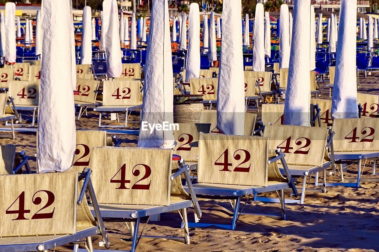 Beach umbrellas with numbered chairs on sand