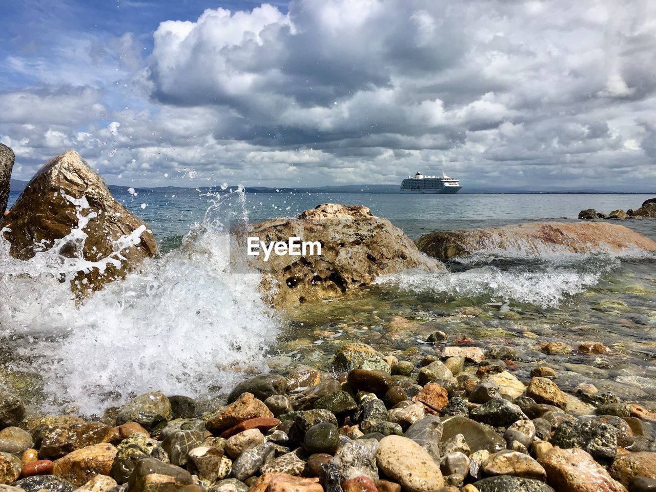 water, sea, rock, cloud - sky, solid, rock - object, sky, beauty in nature, beach, motion, scenics - nature, land, nature, day, wave, aquatic sport, horizon, sport, horizon over water, no people, outdoors, power in nature, breaking, pebble, hitting, rocky coastline
