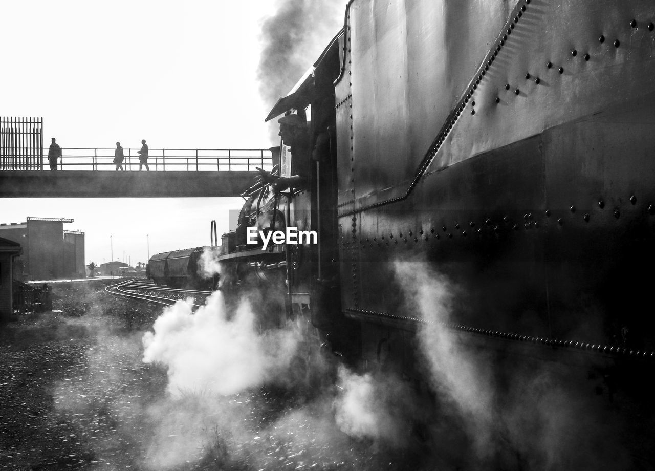 smoke - physical structure, built structure, sky, nature, day, transportation, building exterior, architecture, bridge, industry, steam, cloud - sky, water, pollution, no people, emitting, bridge - man made structure, factory, mode of transportation, outdoors, air pollution