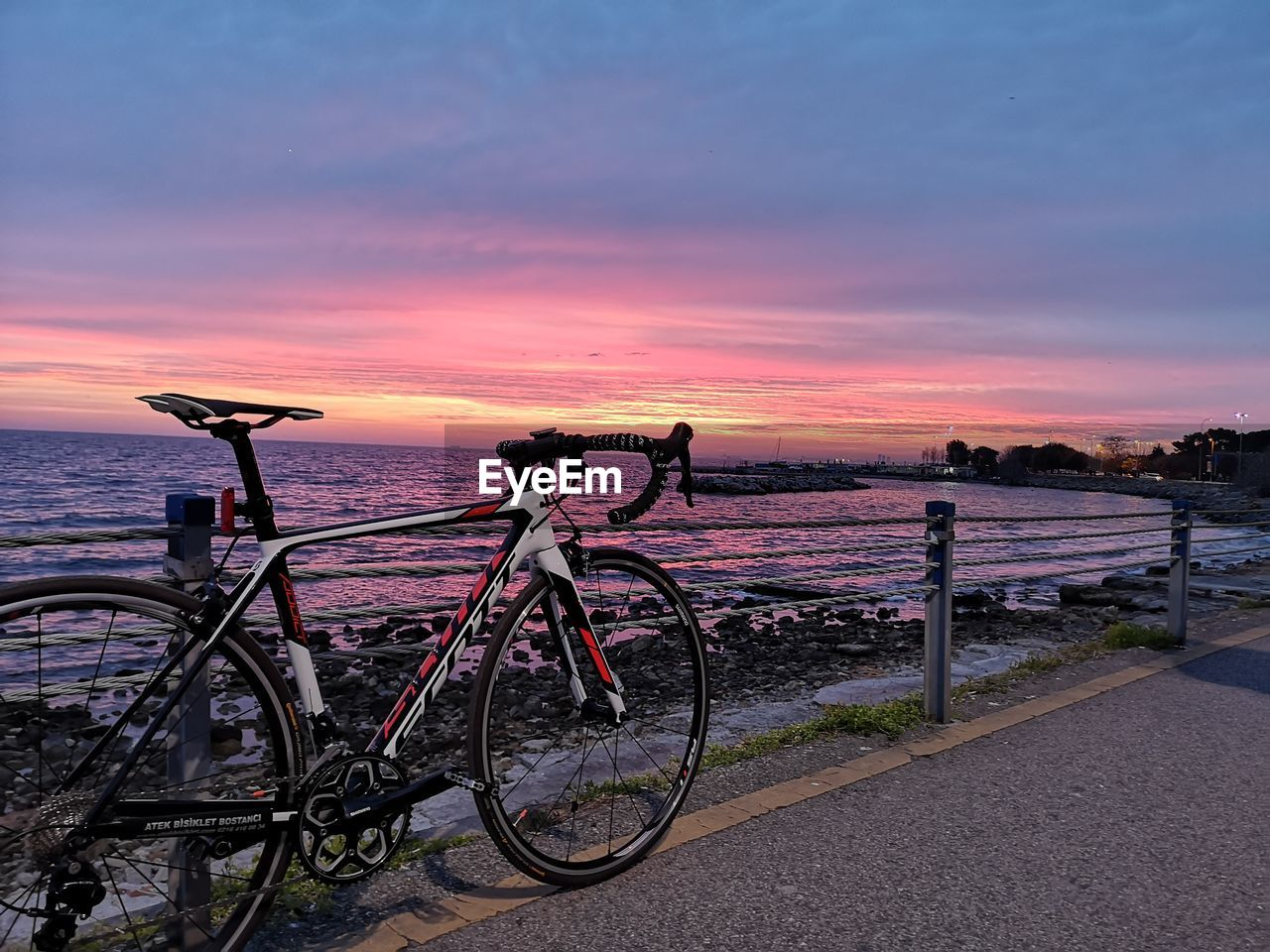 sunset, sky, bicycle, transportation, land vehicle, mode of transportation, cloud - sky, water, beauty in nature, sea, nature, stationary, scenics - nature, railing, no people, orange color, tranquil scene, tranquility, travel, outdoors, purple