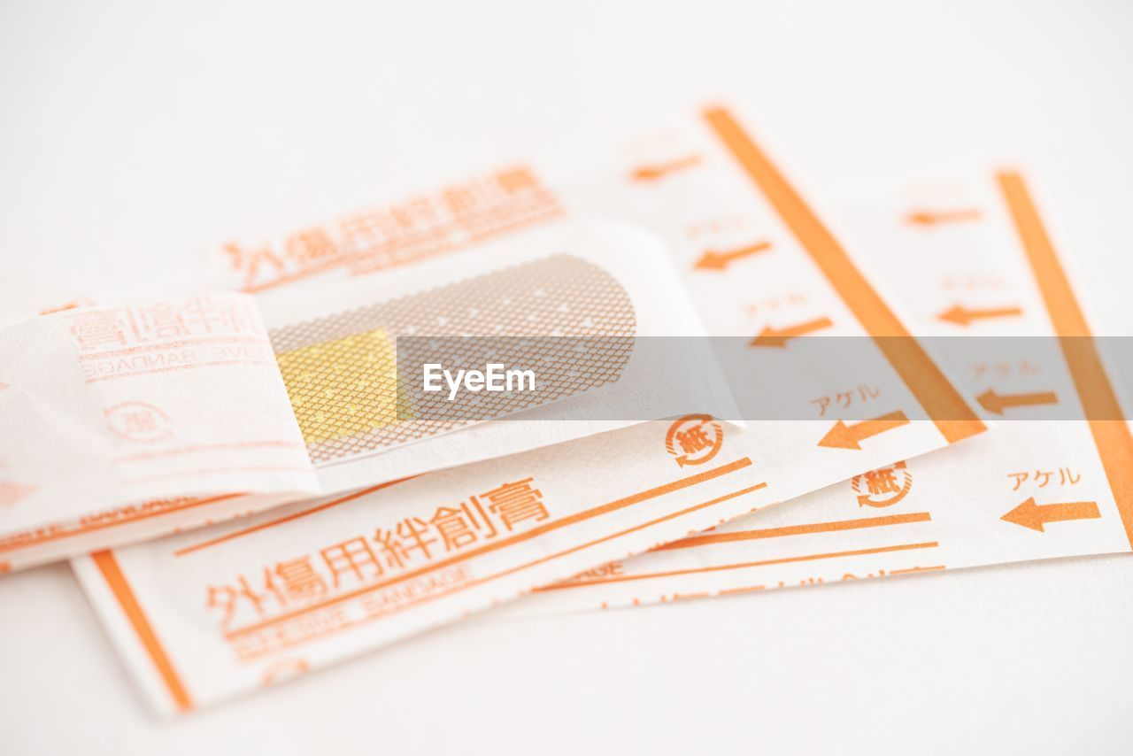 studio shot, still life, indoors, close-up, finance, no people, wealth, white background, currency, paper currency, selective focus, number, business, orange color, cut out, table, high angle view, white color, banking, business finance and industry, economy