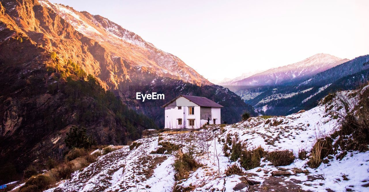 mountain, snow, winter, architecture, cold temperature, built structure, building exterior, building, beauty in nature, house, scenics - nature, sky, mountain range, no people, nature, tranquility, tranquil scene, covering, environment, snowcapped mountain, outdoors, formation, mountain peak