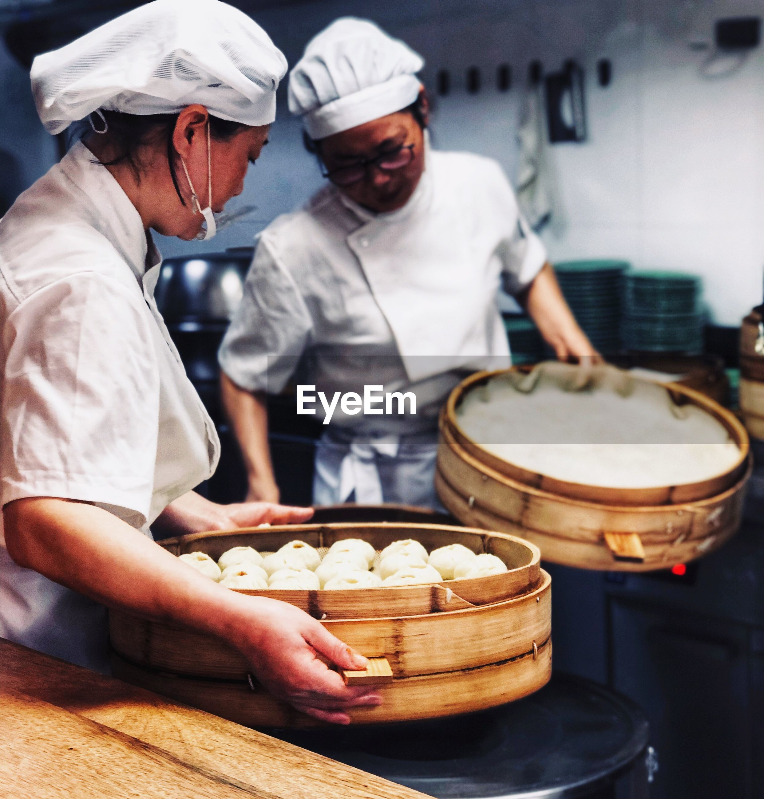 Chefs preparing dumplings in kitchen