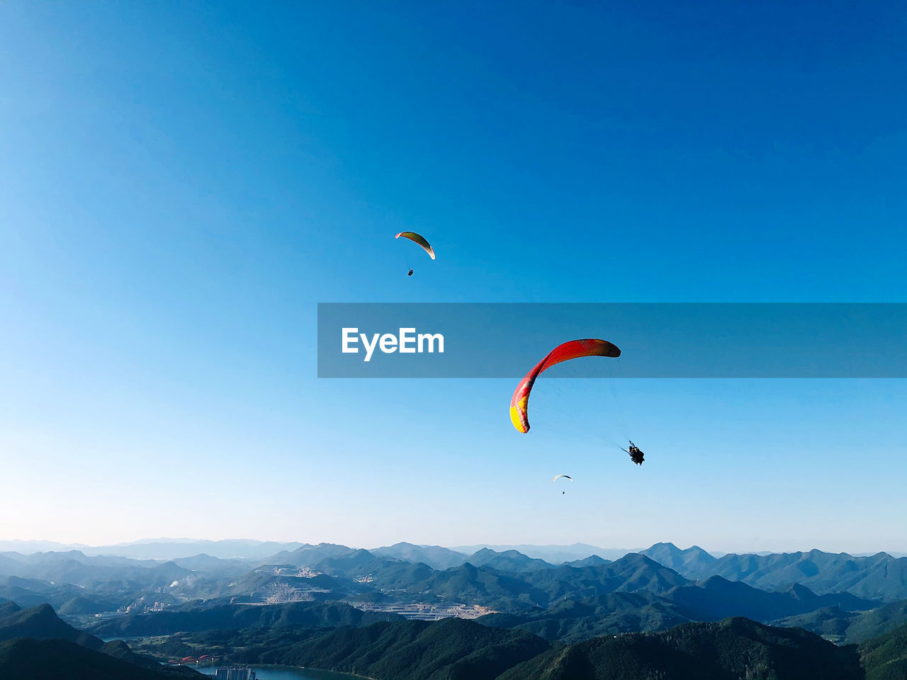Kite flying over mountain against blue sky