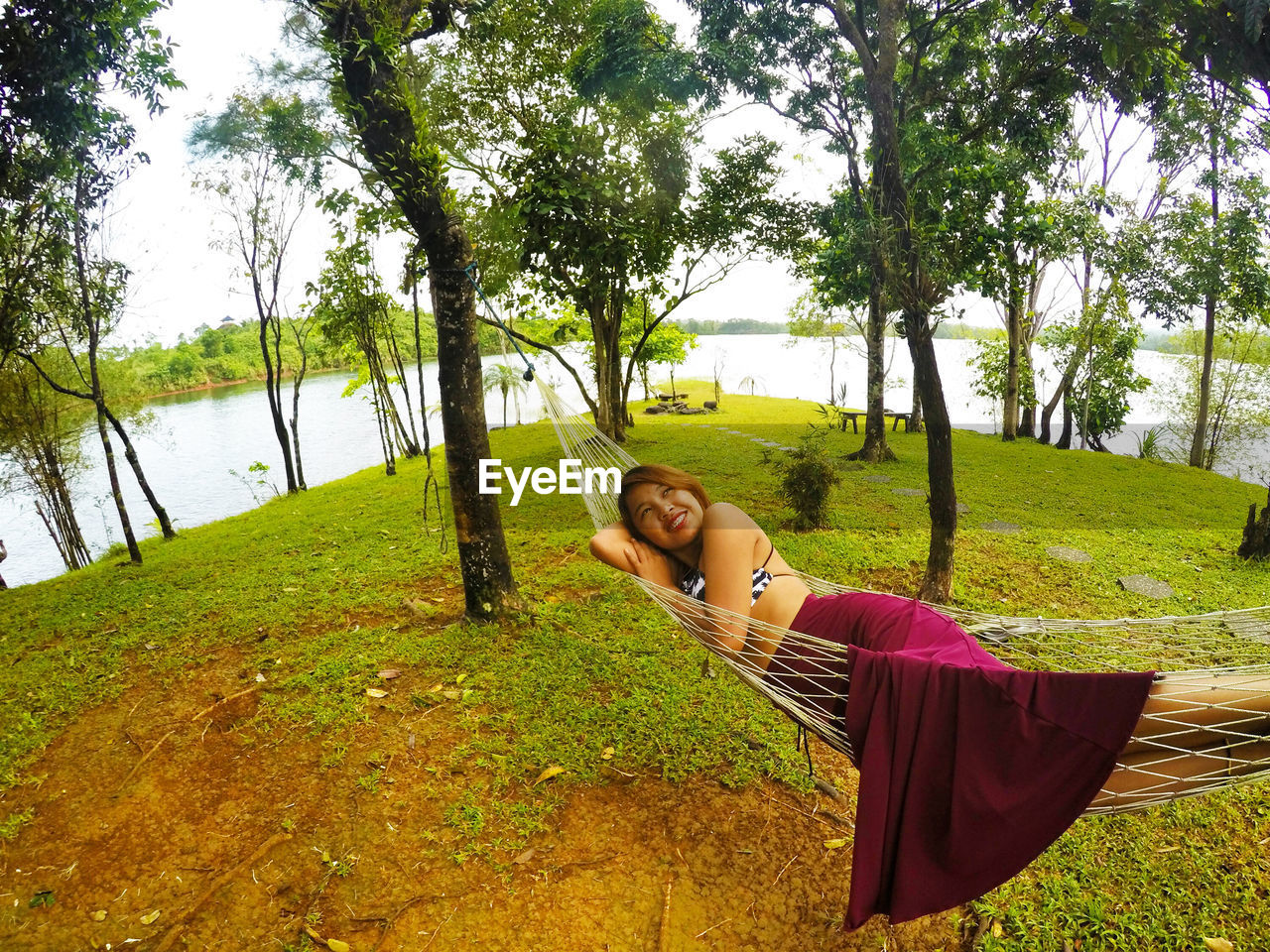 Young woman resting on hammock over field by lake