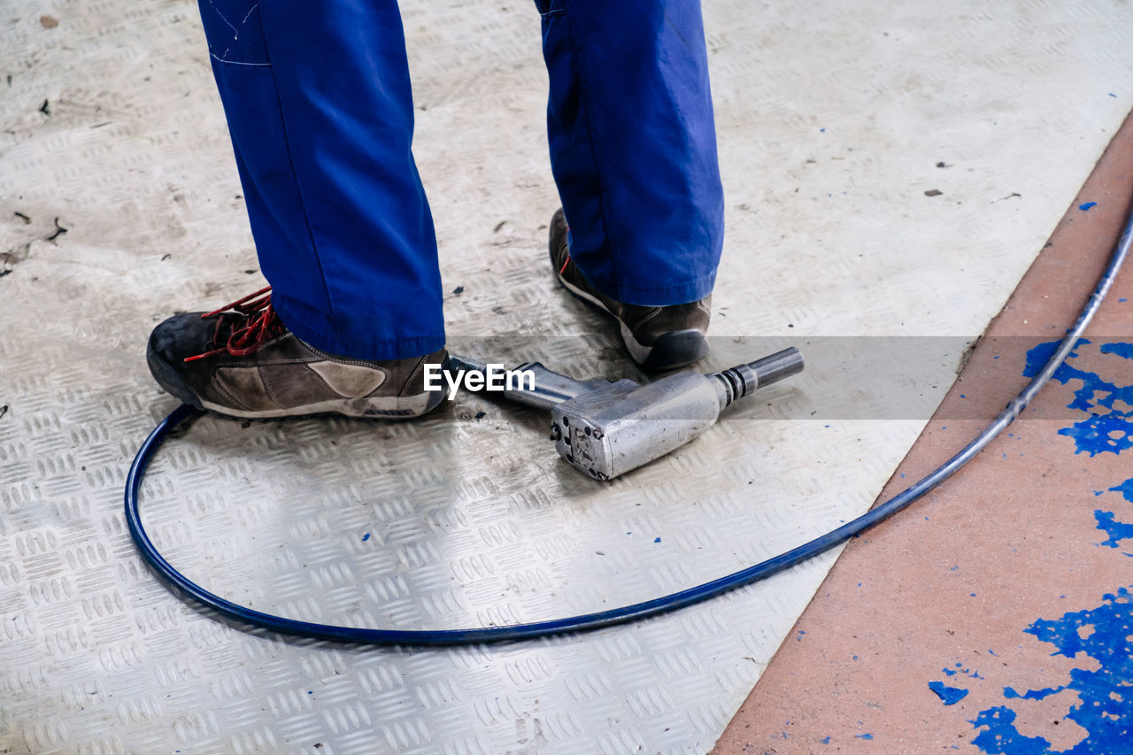 Low Section Of Man With Tool On Ground