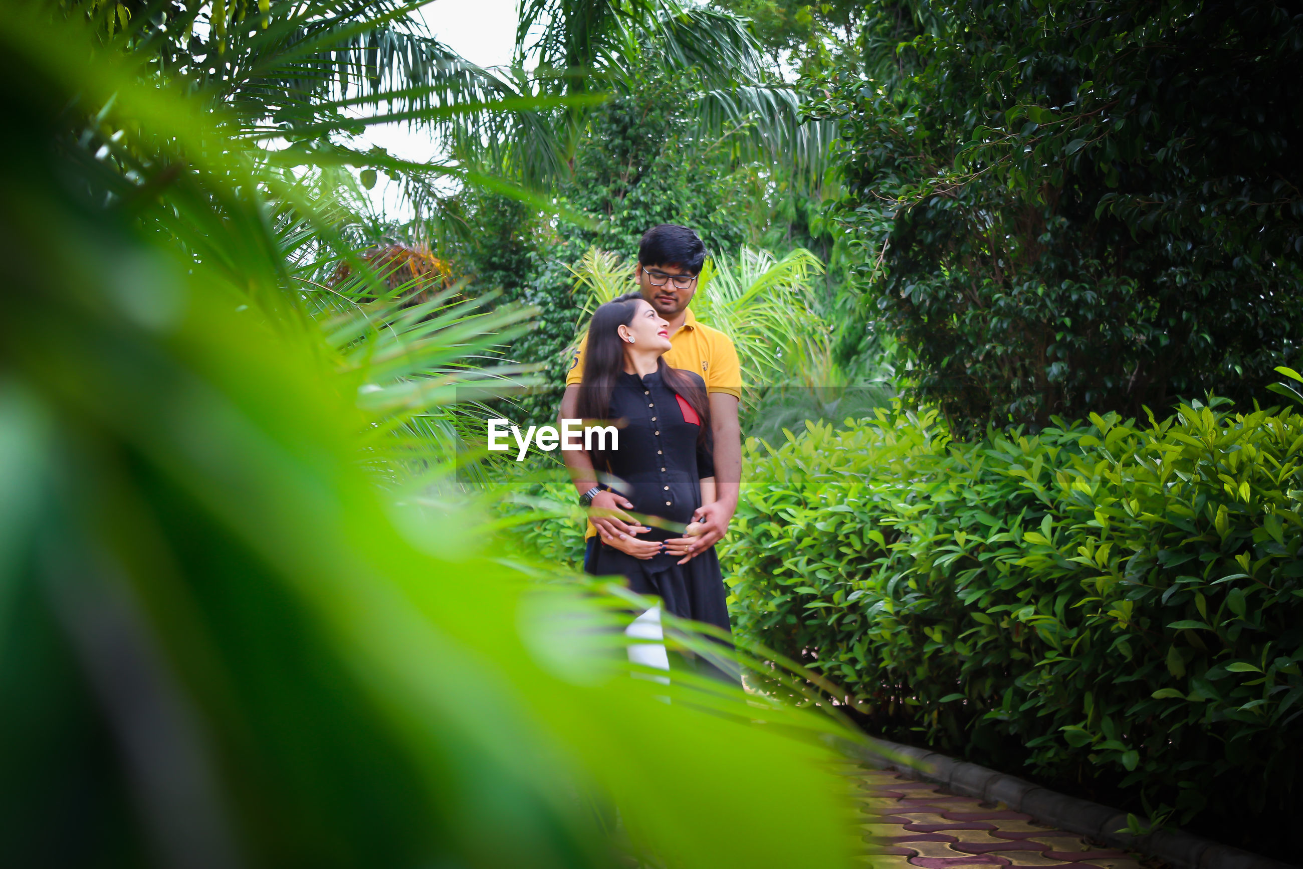 Young man with pregnant woman amidst plants