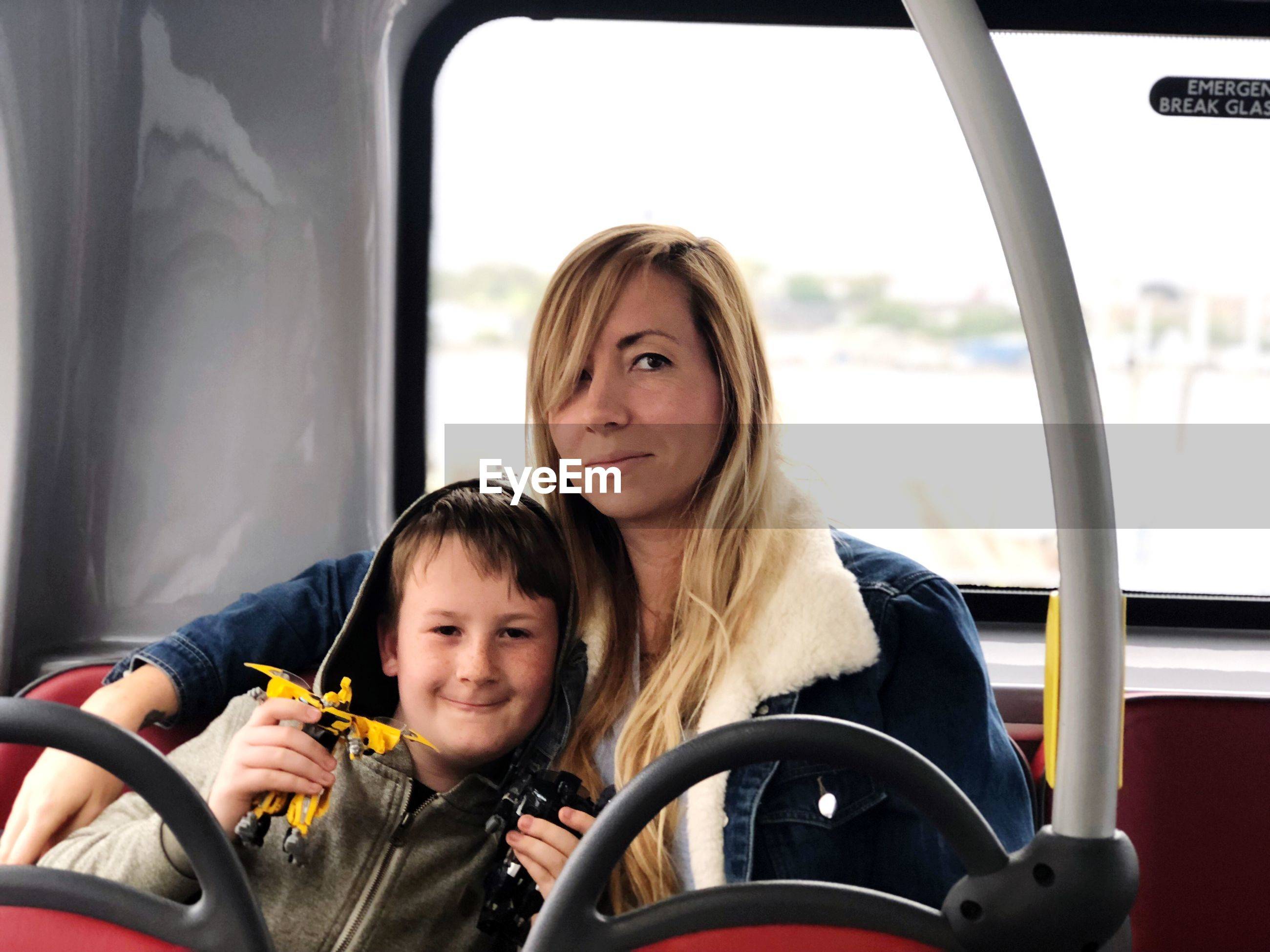 Portrait of woman with son sitting in bus