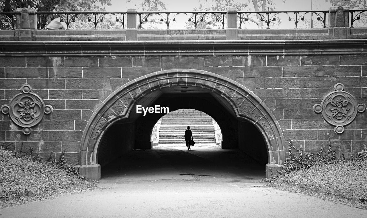 arch, architecture, built structure, one person, real people, lifestyles, entrance, day, direction, building exterior, the way forward, full length, leisure activity, women, tunnel, wall, building, history, the past, outdoors, brick, arched