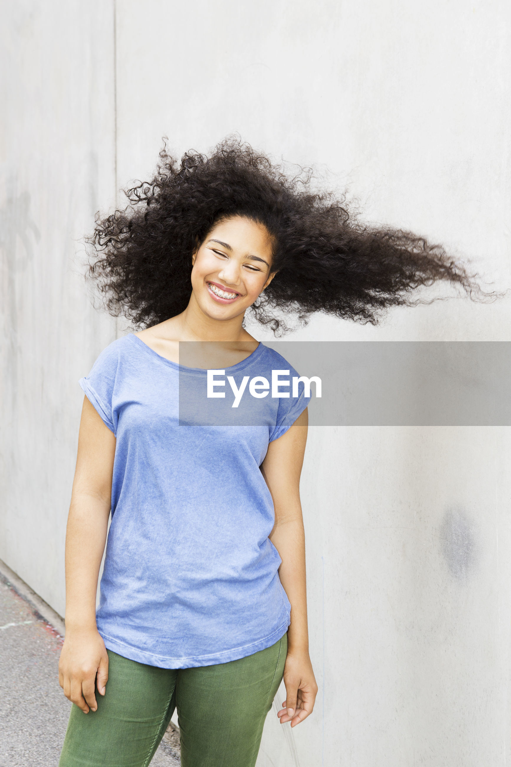 PORTRAIT OF SMILING WOMAN STANDING AGAINST WALL