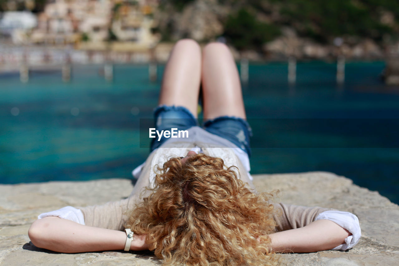 Woman With Curly Blond Hair Resting On Jetty Against River