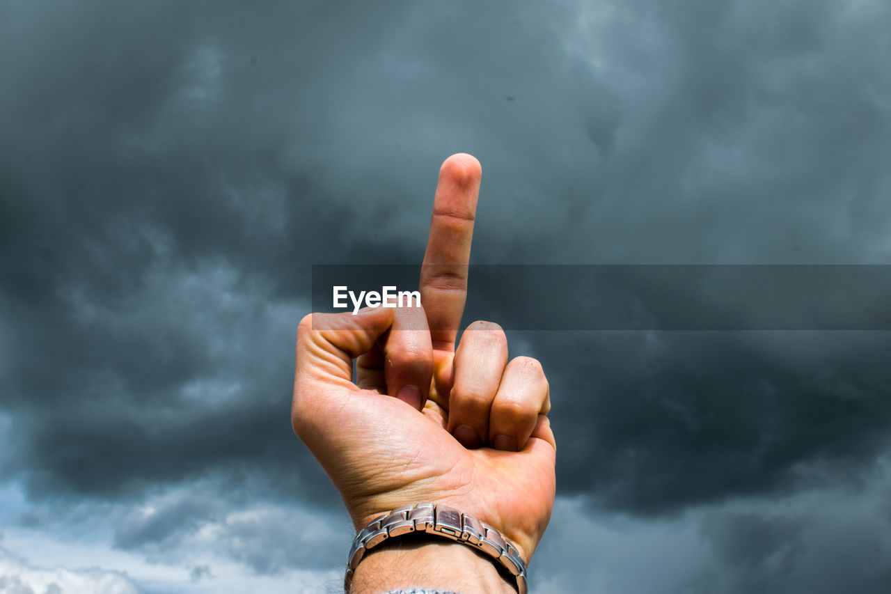 Cropped hand of person showing middle finger against cloudy sky