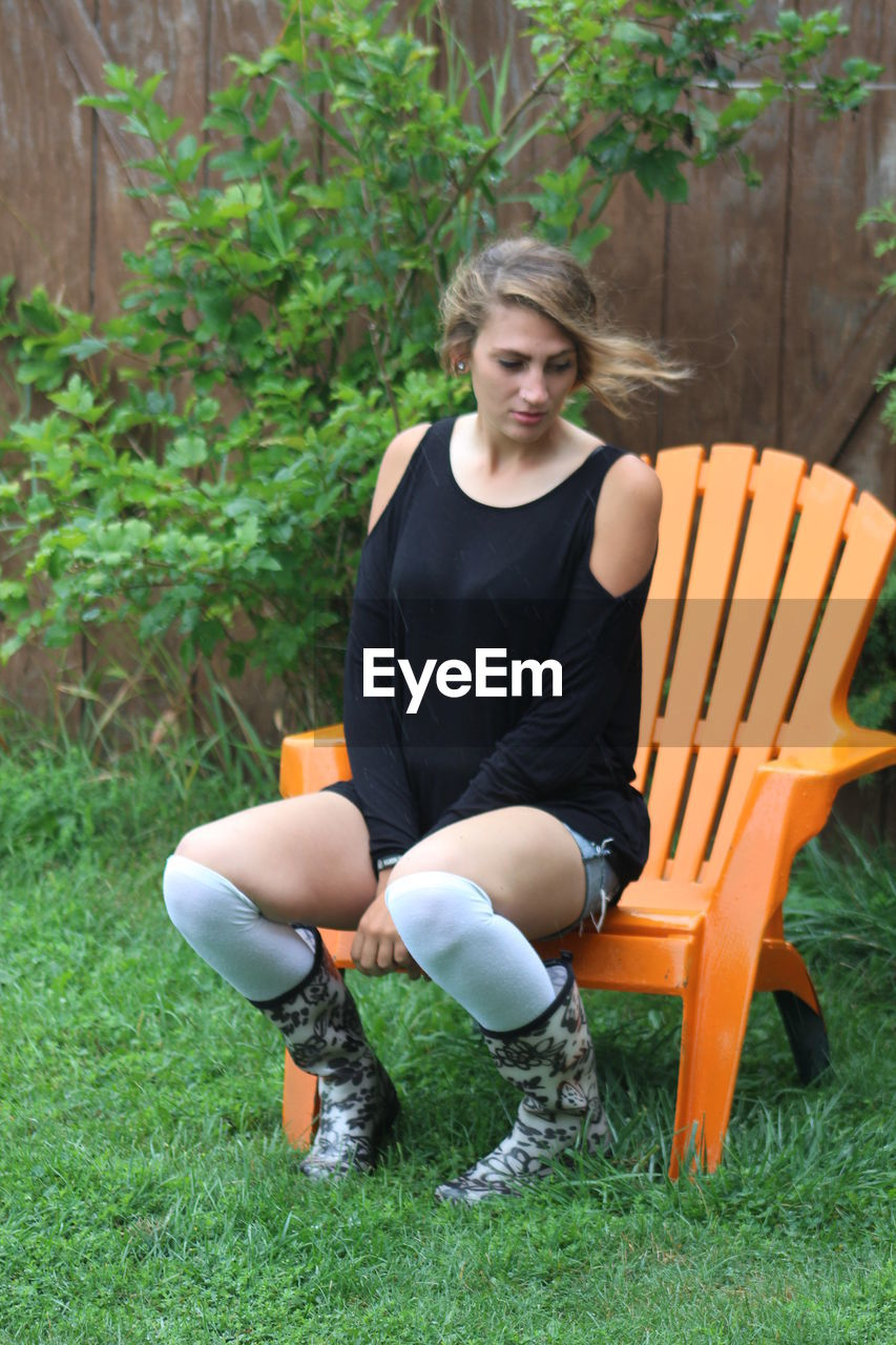 Fashionable young woman sitting on adirondack chair in yard