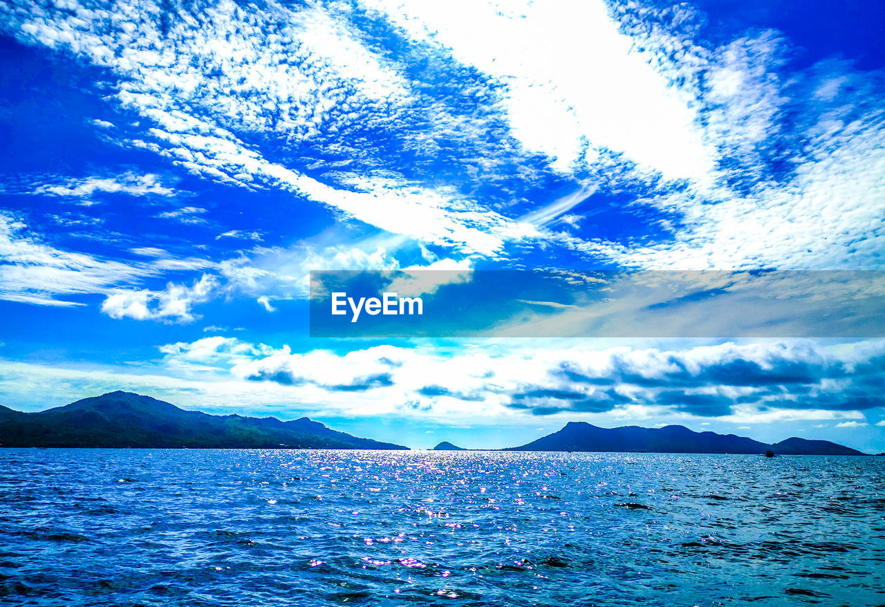 sky, cloud - sky, scenics - nature, water, beauty in nature, tranquil scene, mountain, tranquility, sea, waterfront, nature, blue, no people, idyllic, non-urban scene, mountain range, day, outdoors, remote