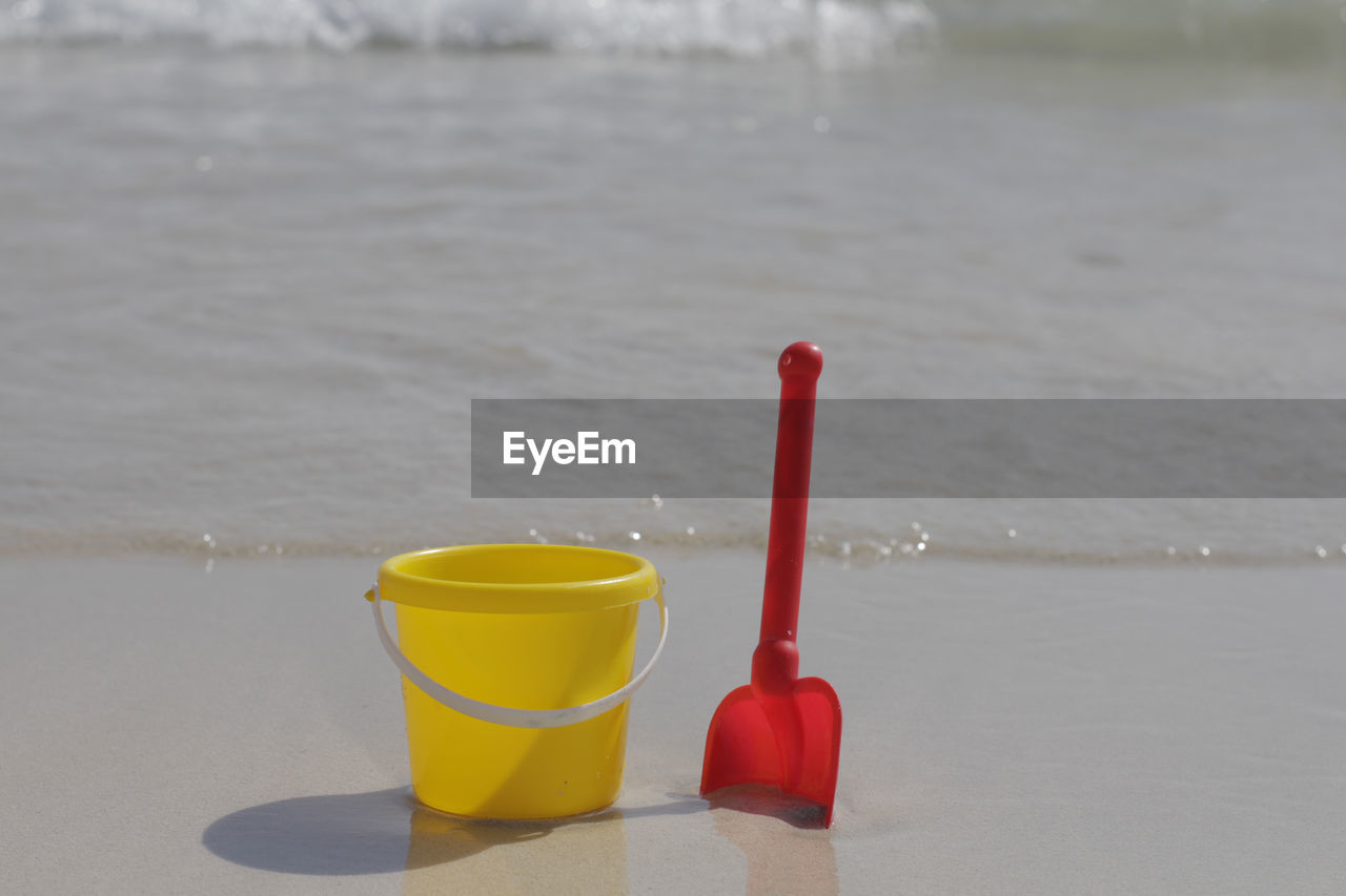 no people, red, yellow, water, focus on foreground, plastic, still life, sea, close-up, day, cup, container, bucket, beach, toy, outdoors, nature, food and drink, freshness