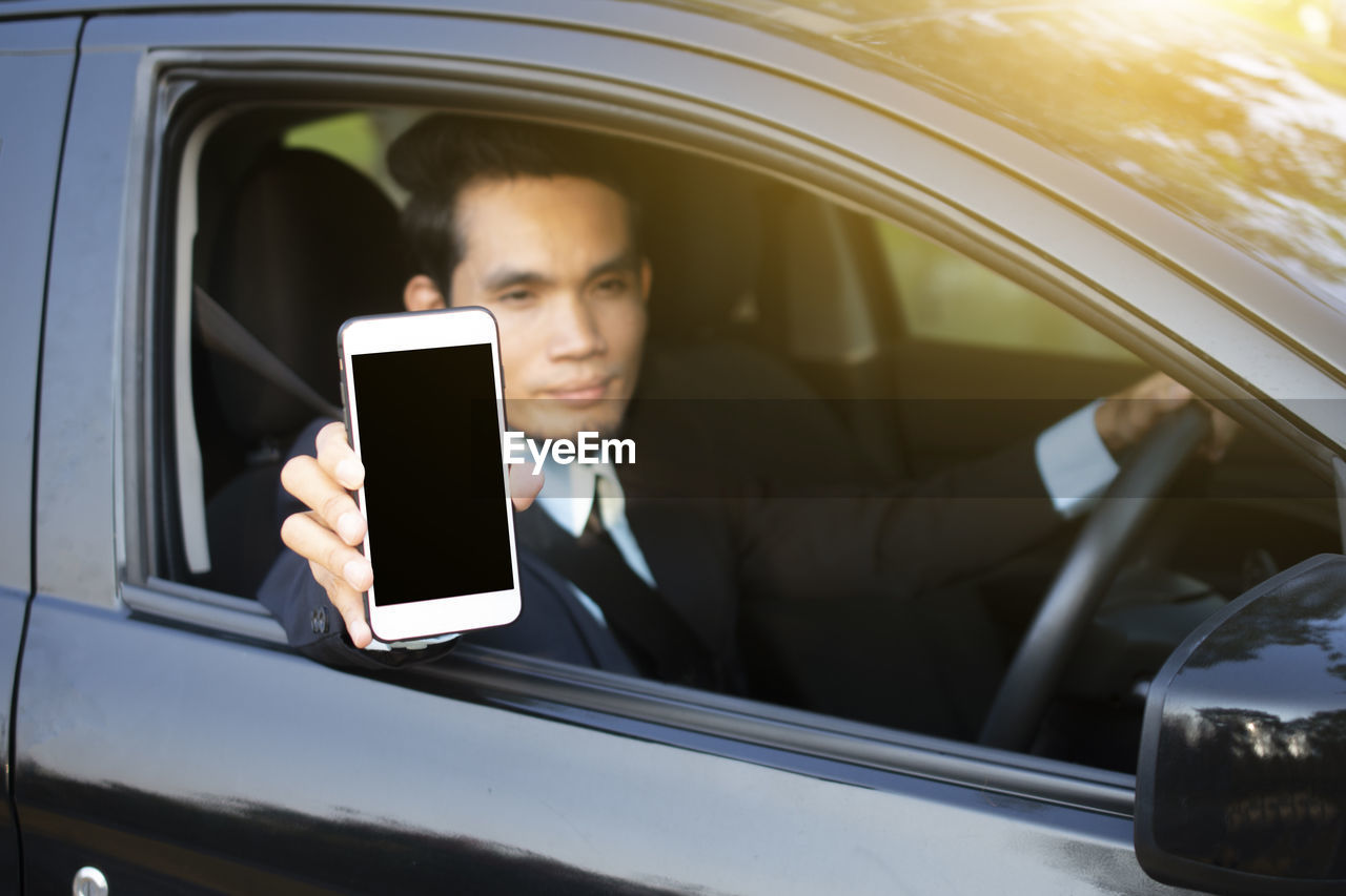 mode of transportation, wireless technology, transportation, technology, motor vehicle, car, land vehicle, communication, one person, mobile phone, smart phone, portable information device, real people, portrait, connection, telephone, lifestyles, headshot, using phone, outdoors