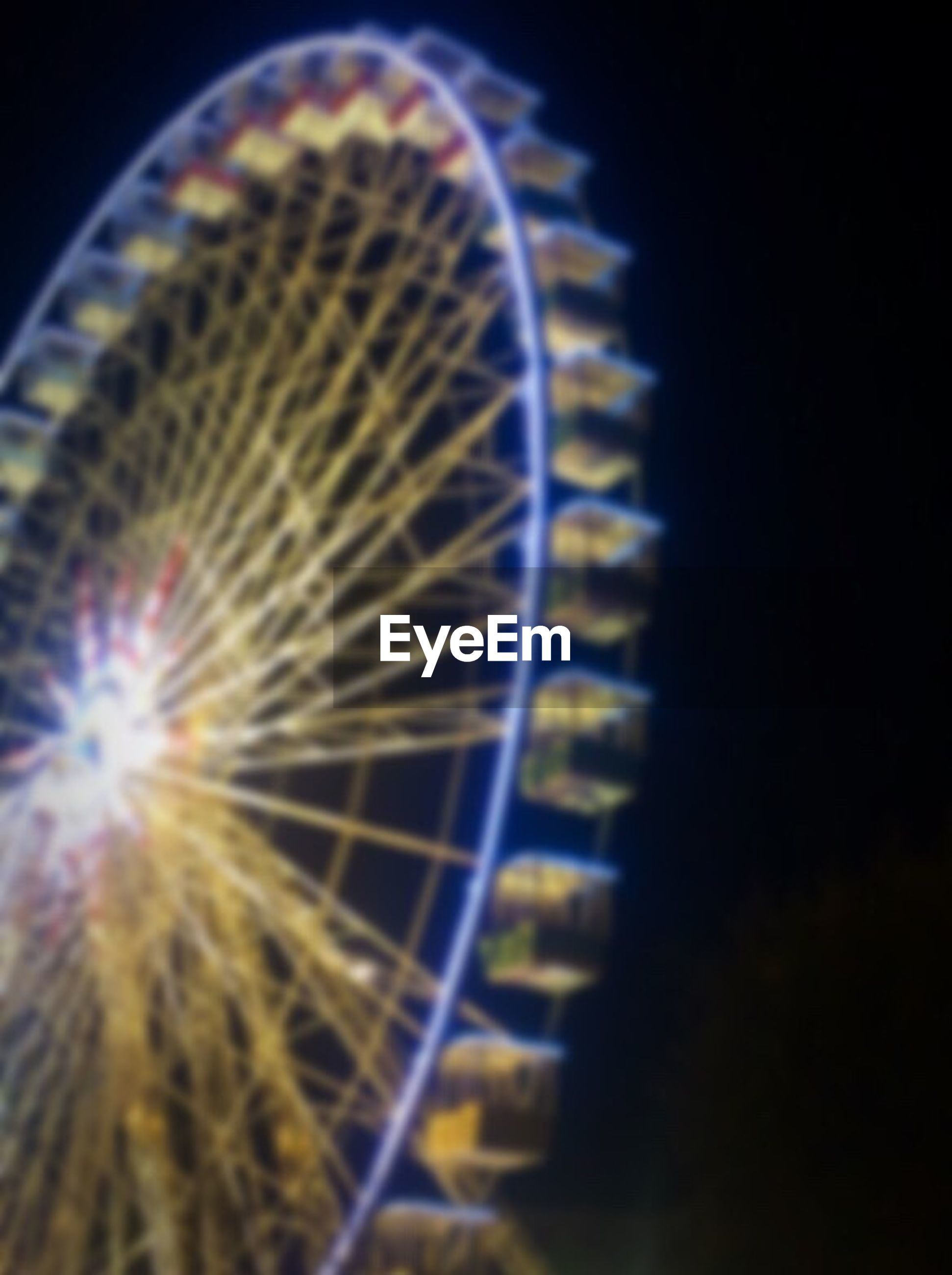 ferris wheel, arts culture and entertainment, amusement park ride, amusement park, night, illuminated, low angle view, sky, circle, motion, outdoors, built structure, long exposure, no people, spinning, glowing, clear sky, blurred motion, architecture, pattern