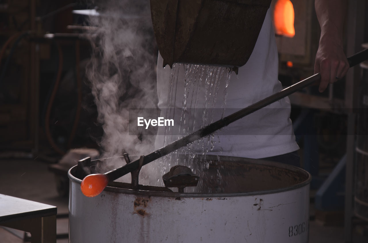 Close-Up Of Man Working In Glass Factory