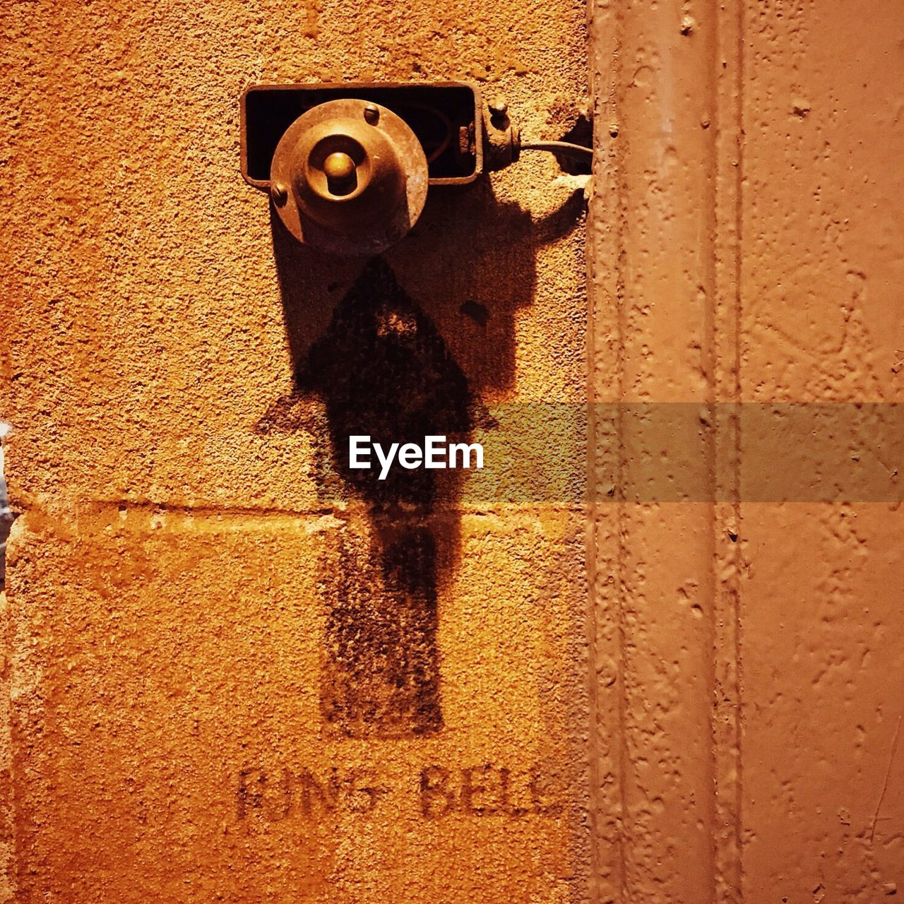 Close-up of old bell with arrow sign wall