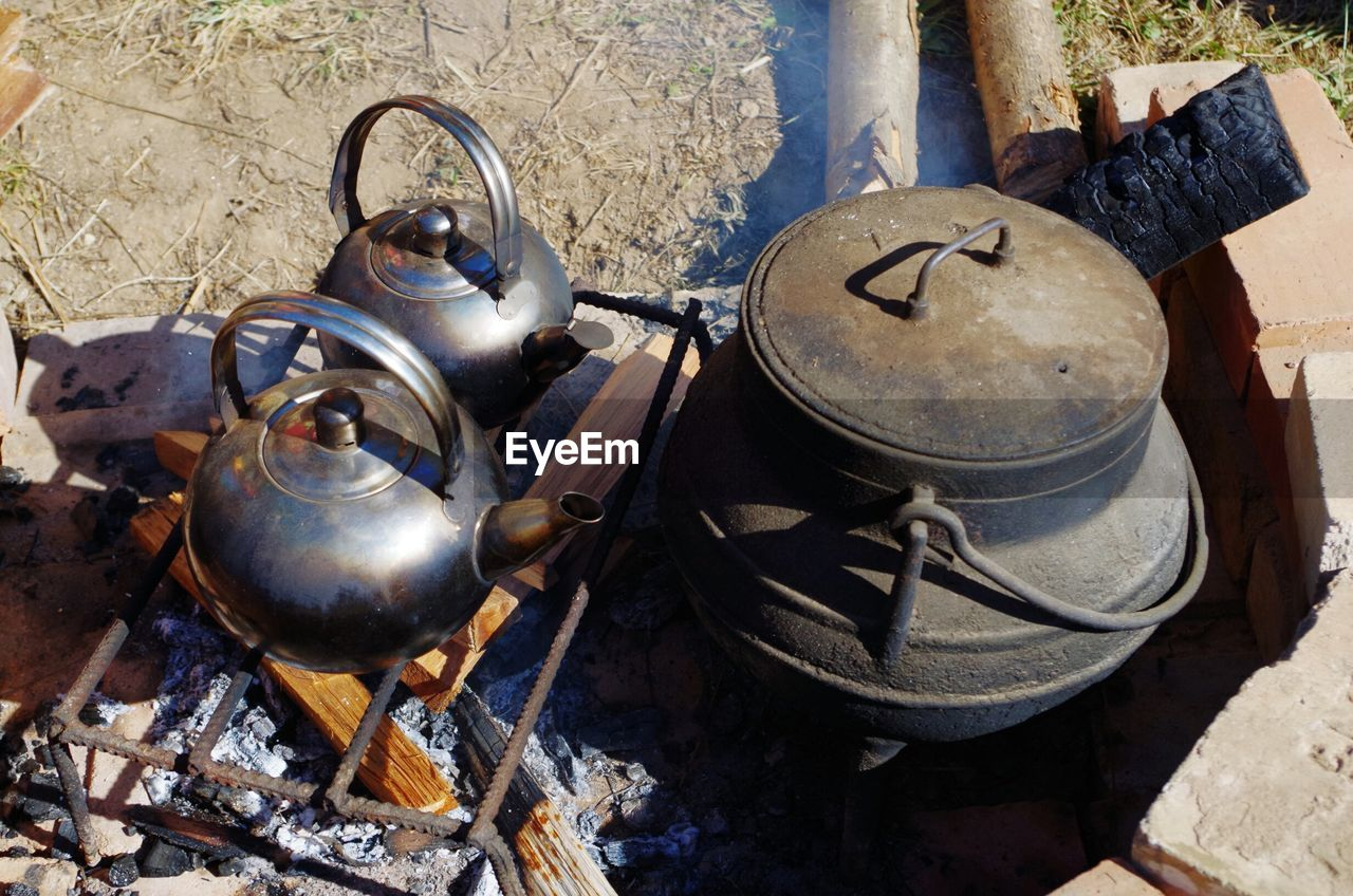 metal, kitchen utensil, household equipment, day, container, kettle, old, no people, high angle view, outdoors, abandoned, rusty, nature, obsolete, architecture, burning, large group of objects, dirt, cooking utensil