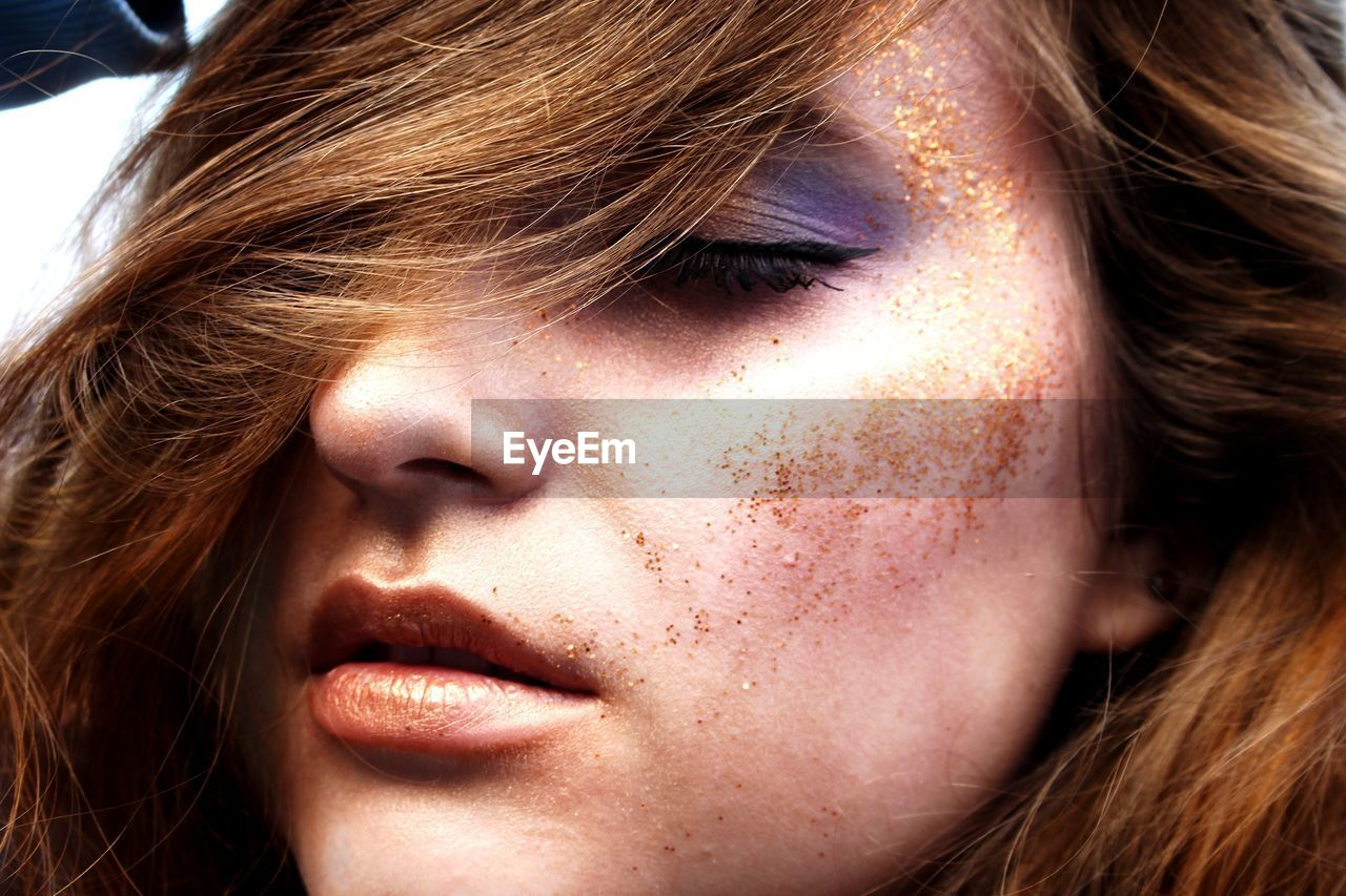 Close-up of beautiful woman with glitter on face