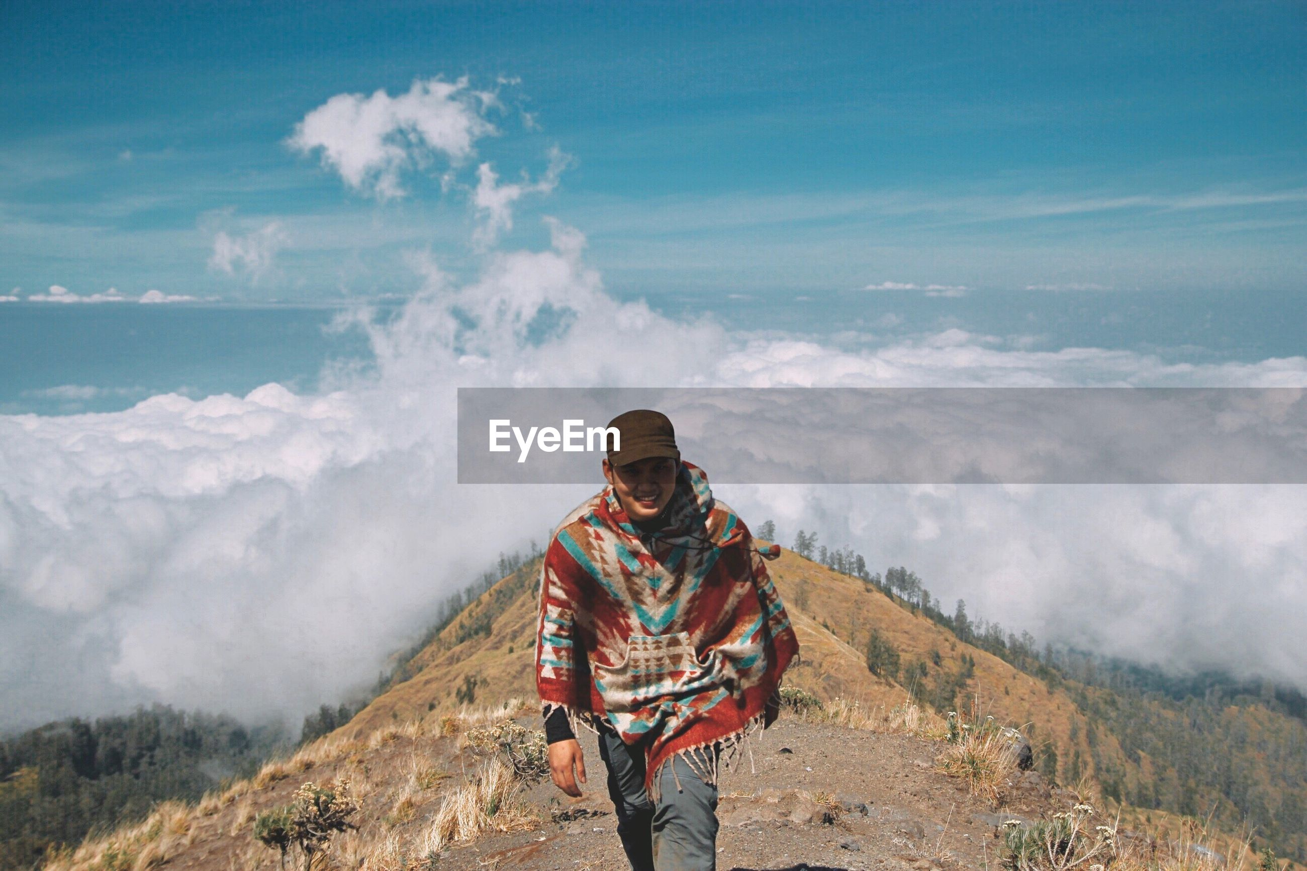 Portrait of young man hiking on mountain against cloudscape