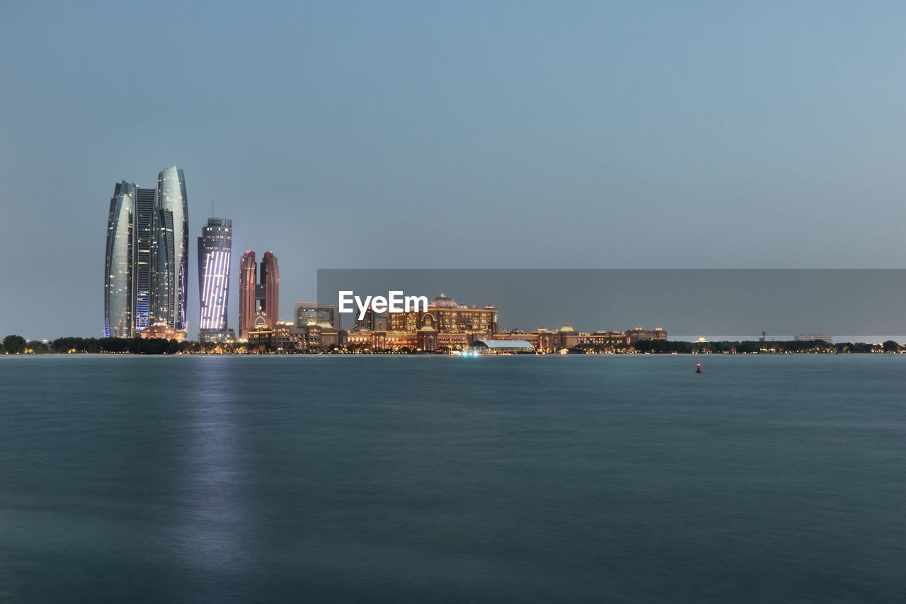 architecture, cityscape, city, building exterior, skyscraper, built structure, waterfront, urban skyline, sea, downtown district, water, modern, sky, travel destinations, outdoors, no people, night, illuminated, clear sky, nature