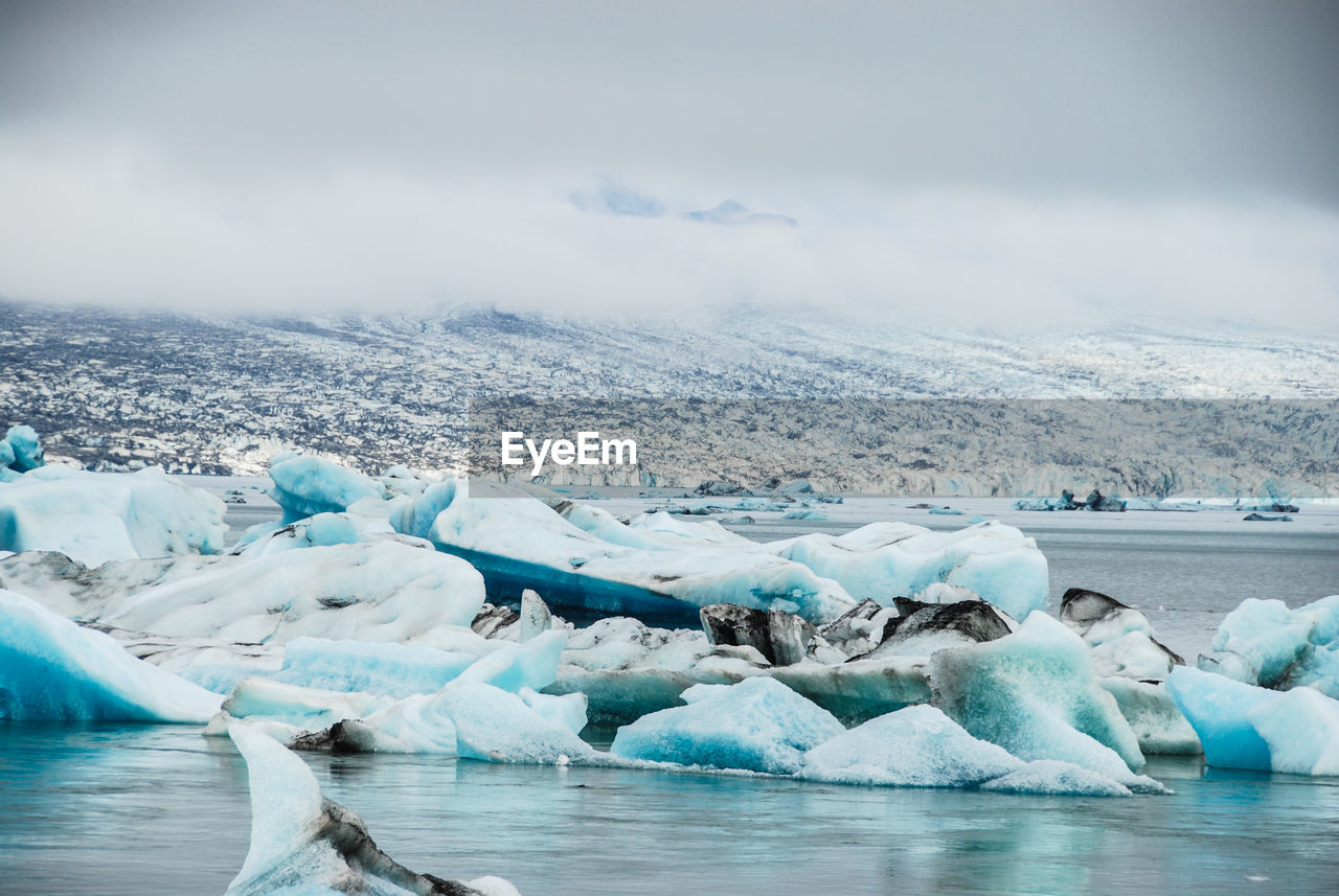 cold temperature, ice, glacier, winter, water, frozen, environment, sky, landscape, scenics - nature, iceberg, tranquil scene, snow, tranquility, cloud - sky, nature, beauty in nature, day, no people, outdoors, floating on water, melting, lagoon, frozen water