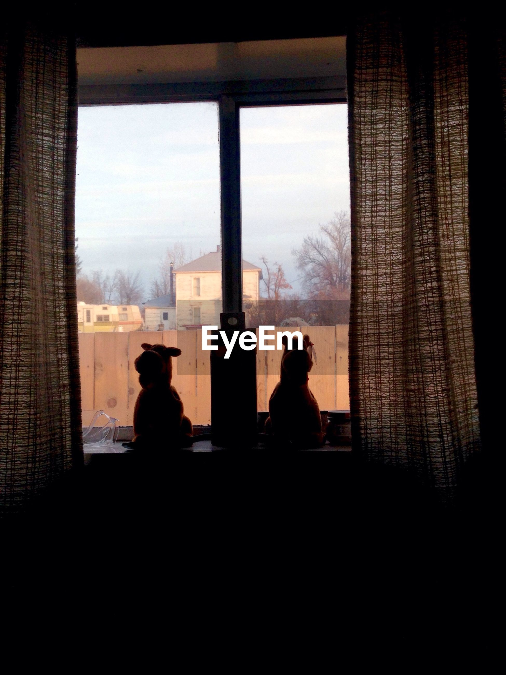 Silhouette stuffed toys on window sill against built structure