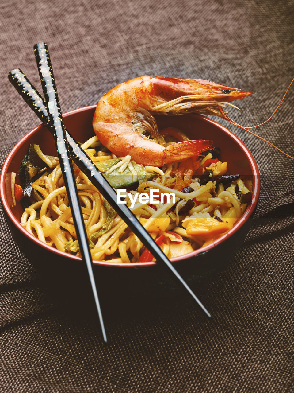 Close-Up Of Prawn And Noodles In Bowl With Chopsticks