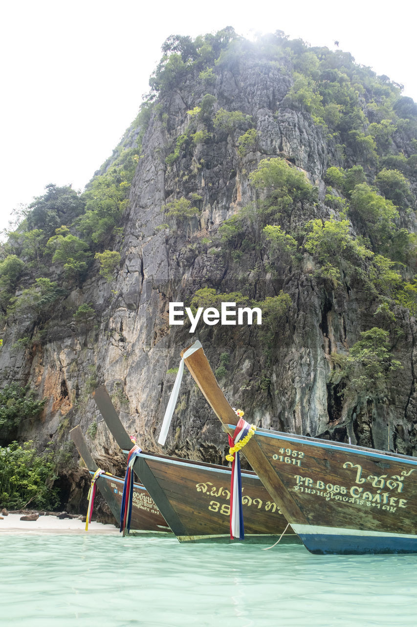 mountain, nautical vessel, mode of transportation, transportation, nature, water, scenics - nature, day, beauty in nature, rock, land, rock - object, mountain range, tree, longtail boat, sky, tranquility, rock formation, no people, outdoors, formation