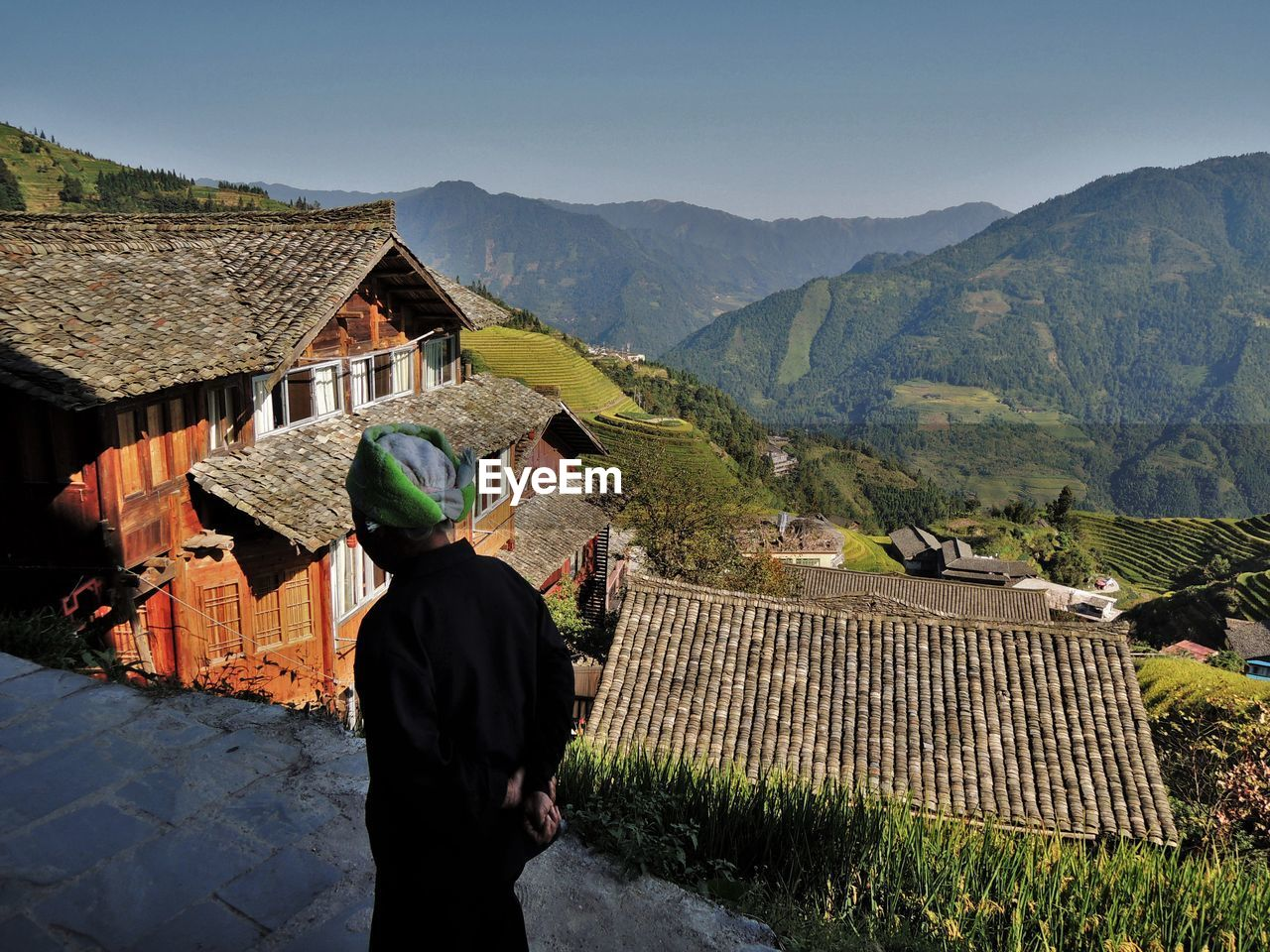 REAR VIEW OF MAN STANDING BY HOUSES ON MOUNTAIN