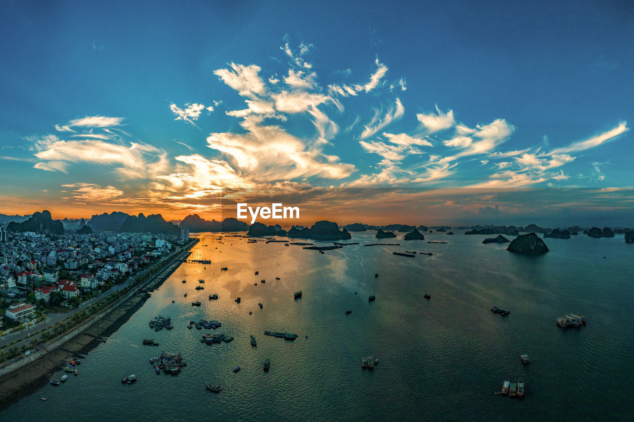 Aerial view of sea against blue sky during sunset