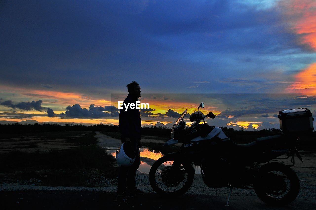 sunset, sky, silhouette, real people, cloud - sky, orange color, transportation, men, one person, mode of transport, outdoors, land vehicle, standing, nature, motorcycle, scenics, beauty in nature, full length, water, day, people