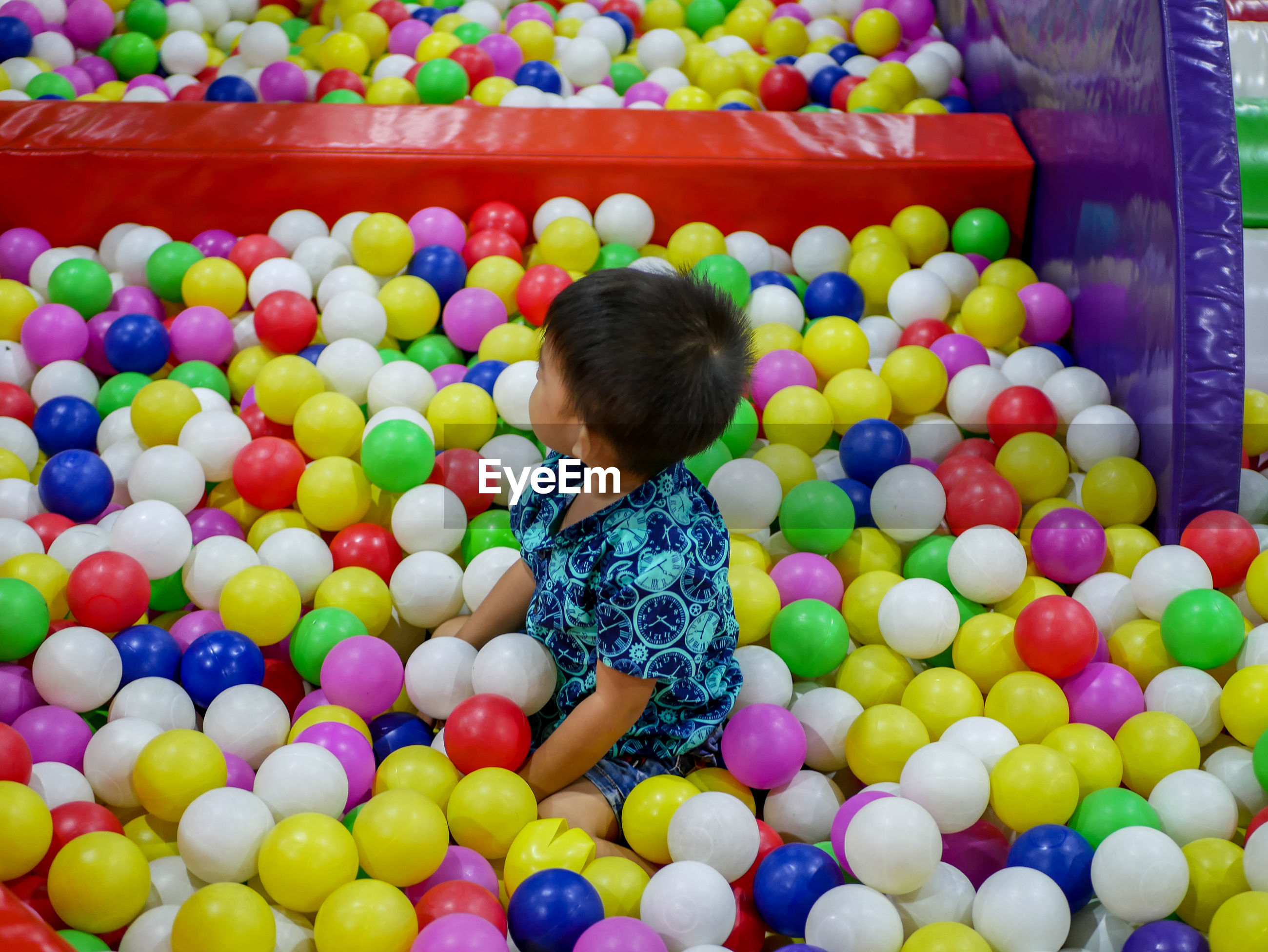 High angle view of boy playing in ball pool