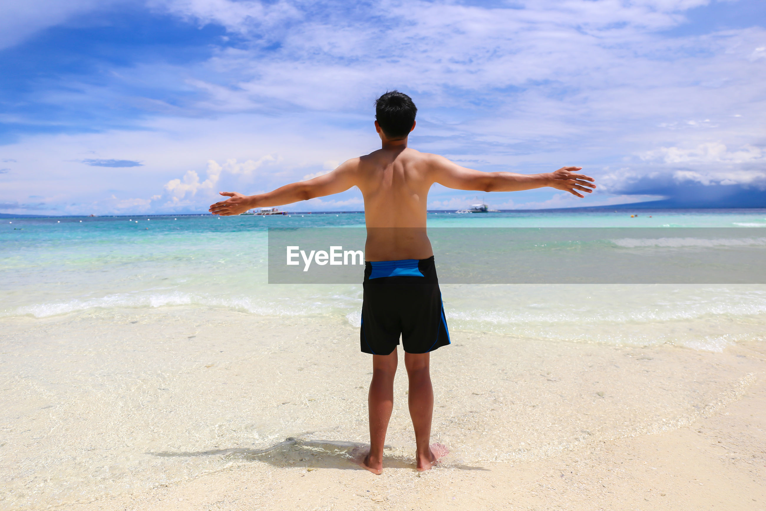 Rear view of shirtless man with arms outstretched standing at beach against sky