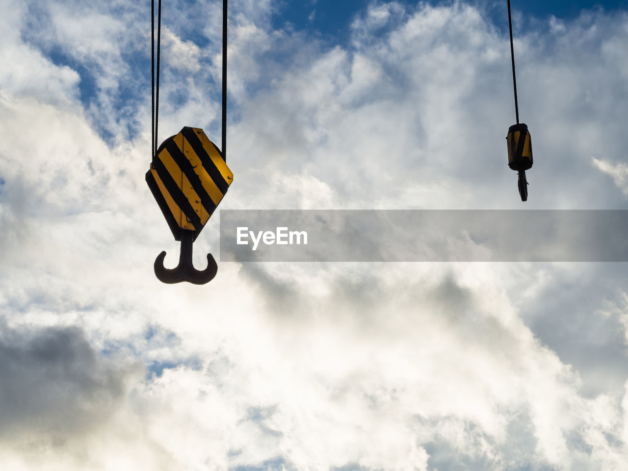 Hooks of construction crane against dramatic cloudy sky