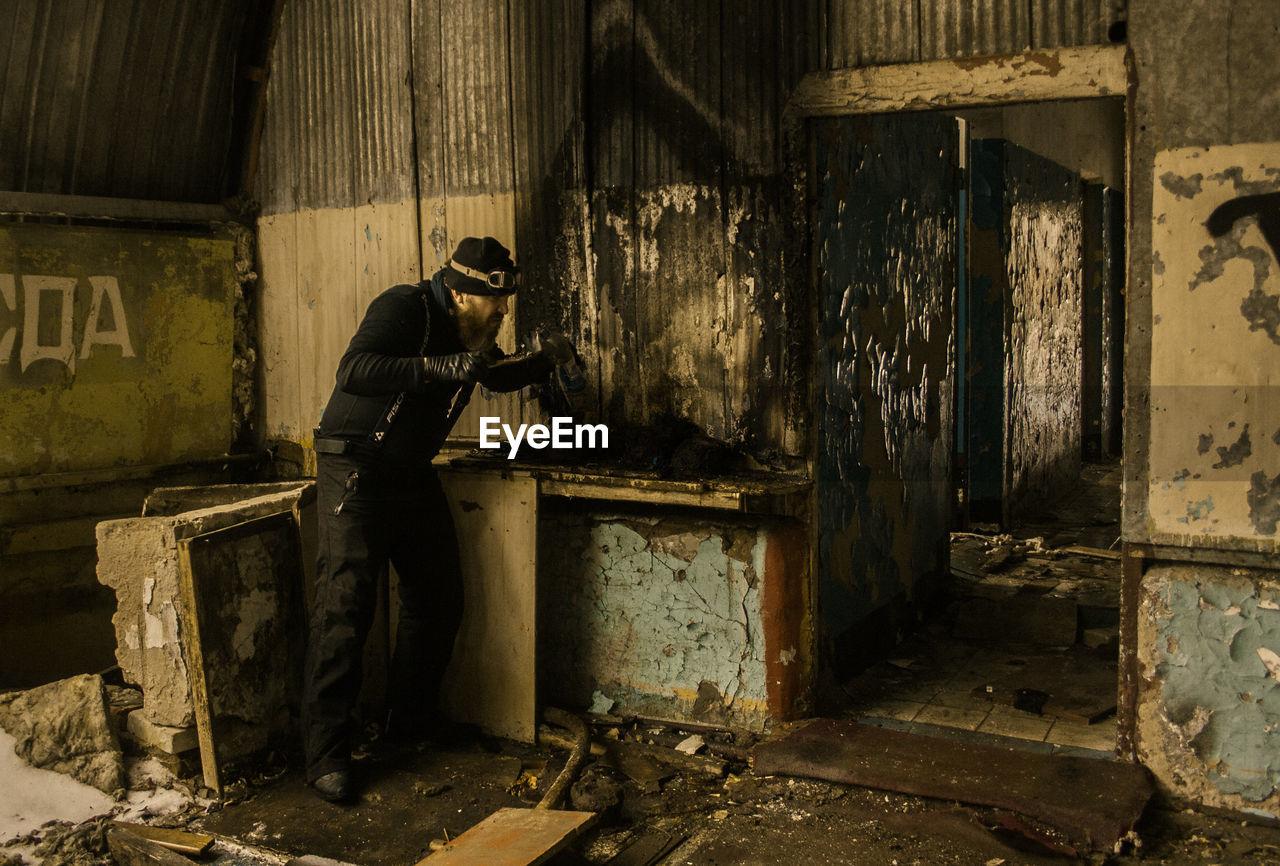 Full length of man standing in abandoned room
