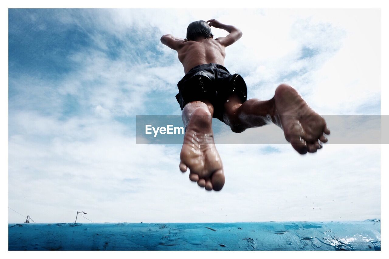 Low Angle View Of Man Jumping In Sea Against Cloudy Sky