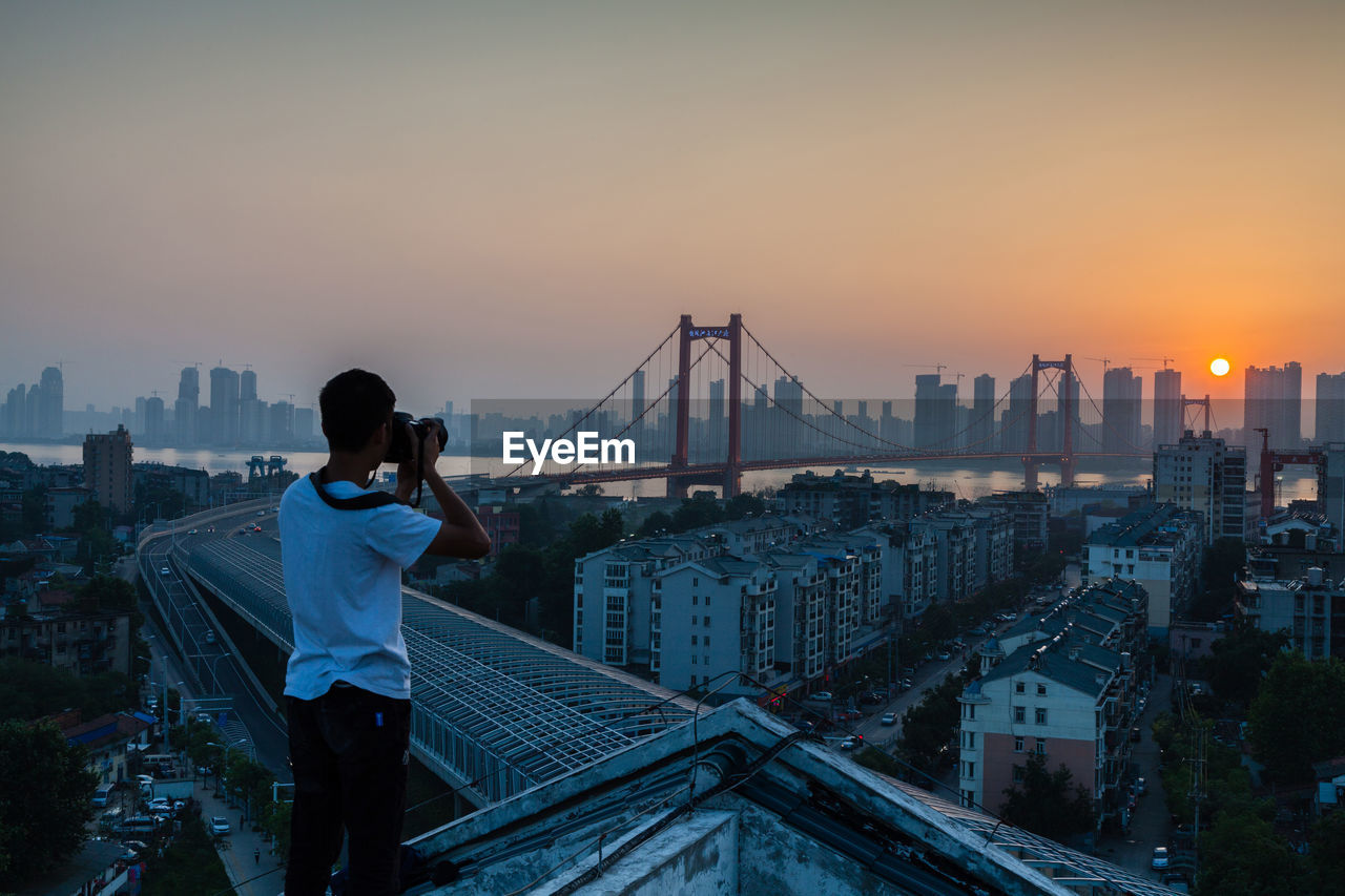 Rear View Of Man Photographing Bridge Over River During Sunset