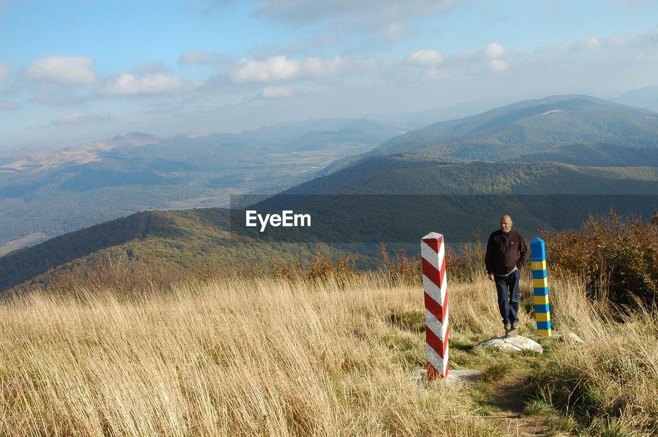 Full length of man standing on mountain peak against landscape