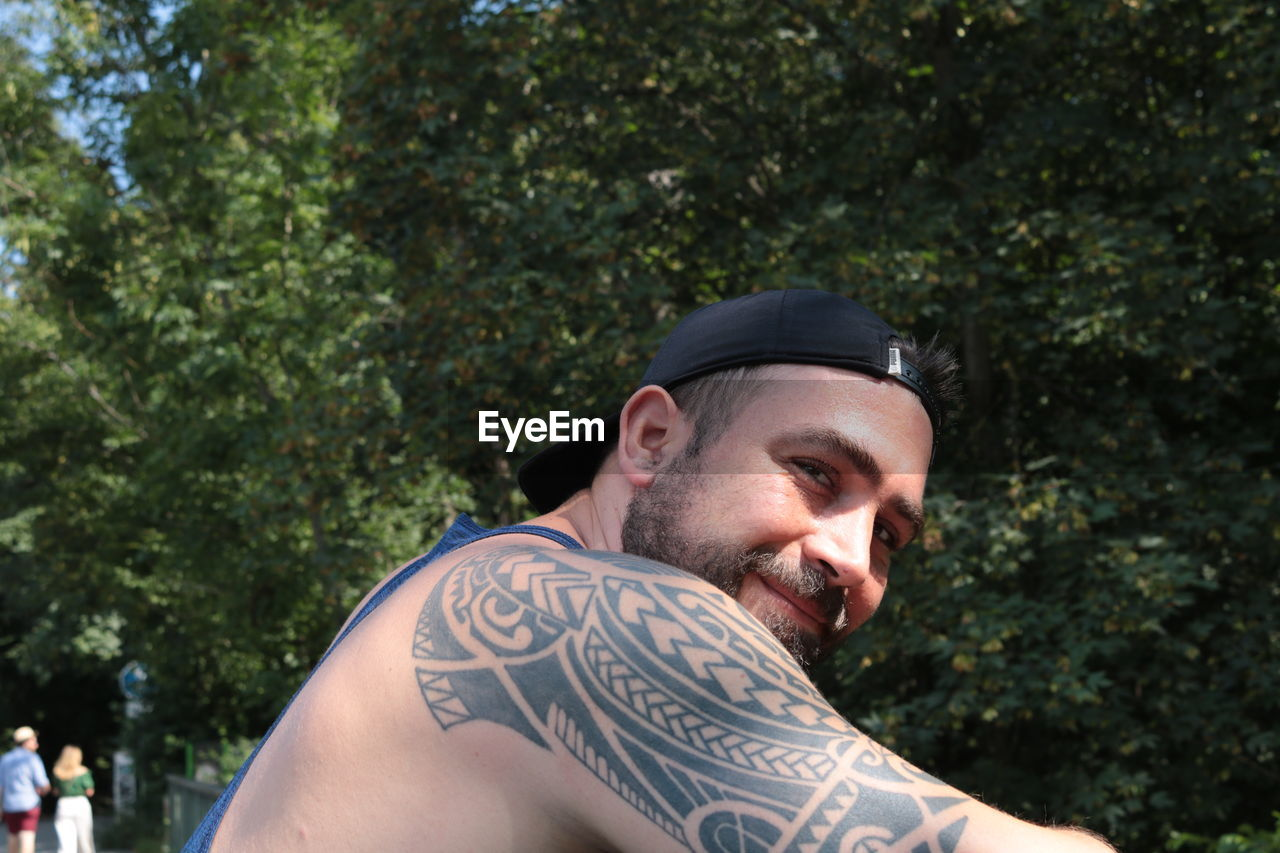 Portrait of shirtless man against trees
