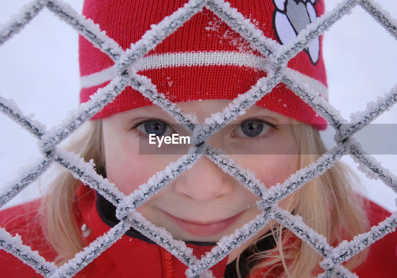 Close-Up Portrait Of Teenage Girl Looking Through Frozen Fence