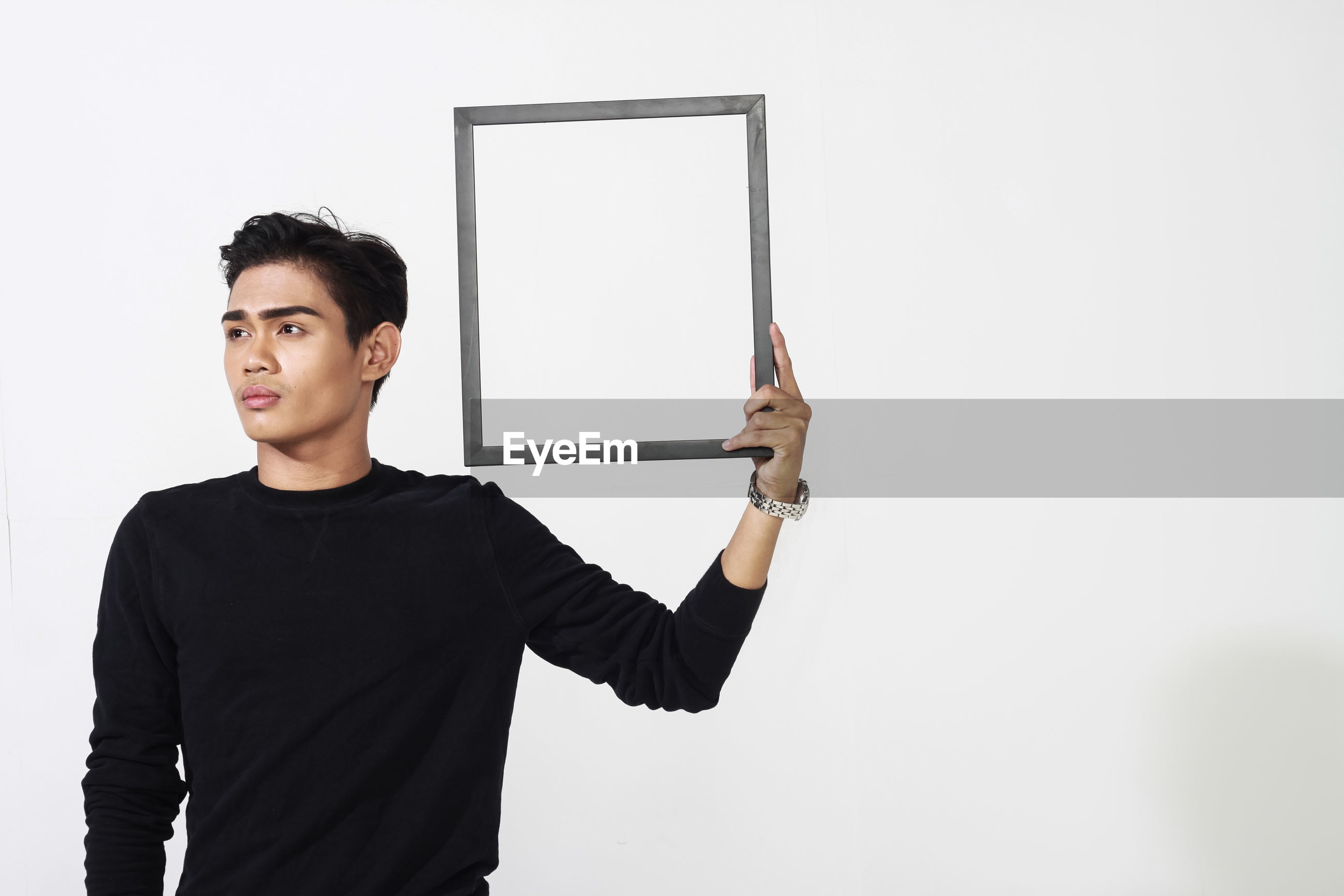 Young man holding frame while standing against white background