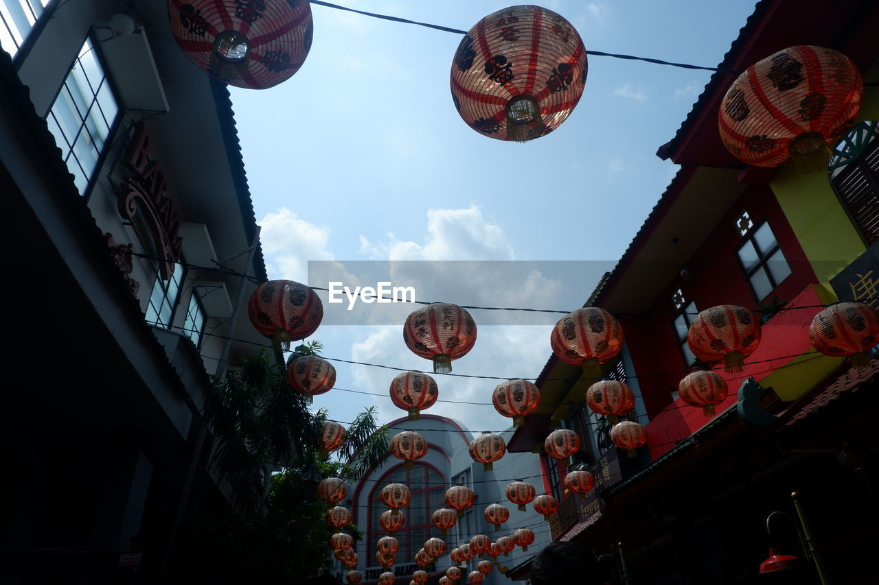 low angle view, built structure, building exterior, architecture, hanging, sky, decoration, no people, lantern, lighting equipment, chinese lantern, cloud - sky, in a row, day, nature, large group of objects, outdoors, building, city