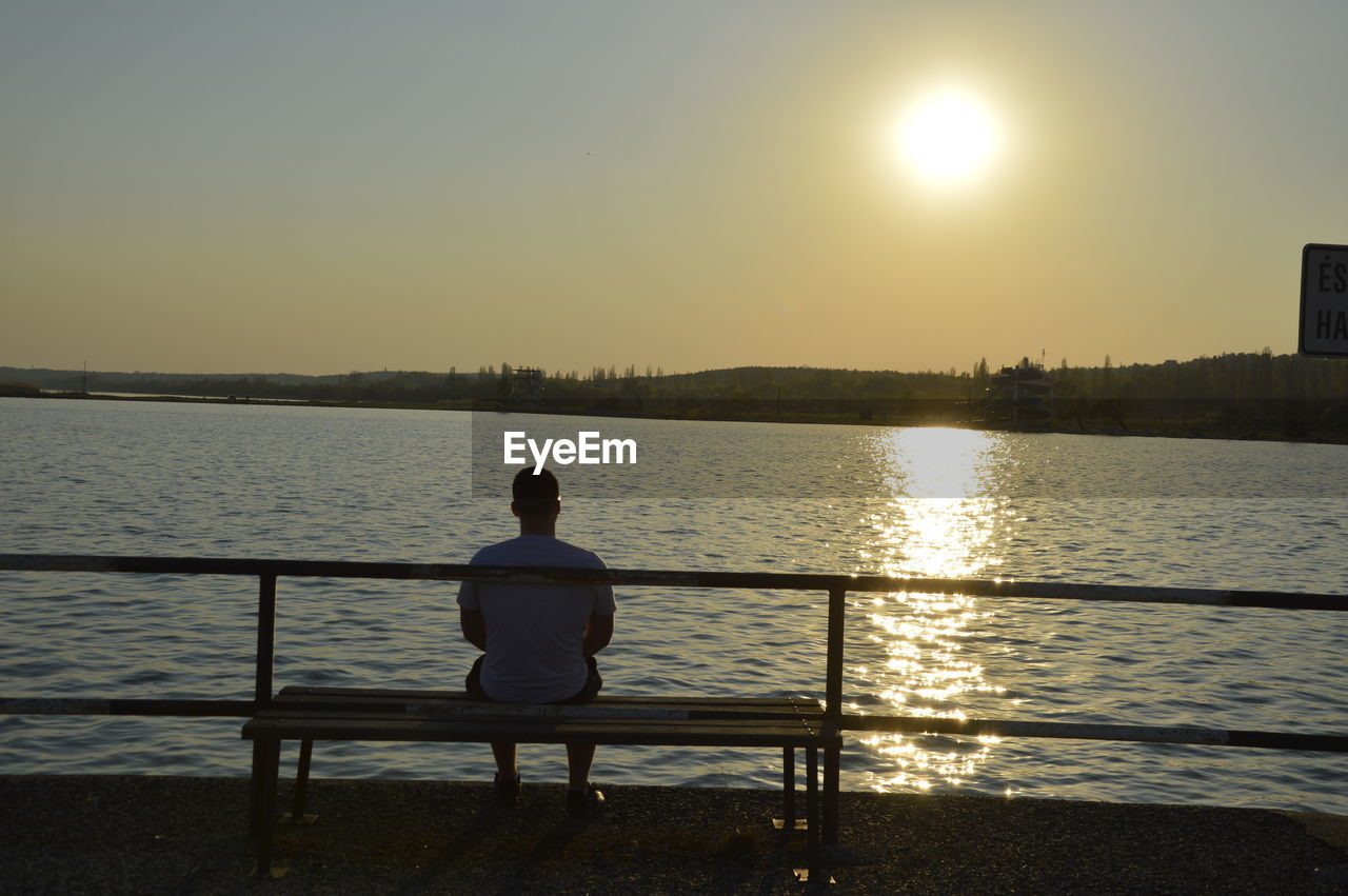 water, sunset, rear view, sunlight, sitting, sun, relaxation, tranquil scene, nature, scenics, one person, beauty in nature, tranquility, sea, real people, clear sky, outdoors, sky, day, people