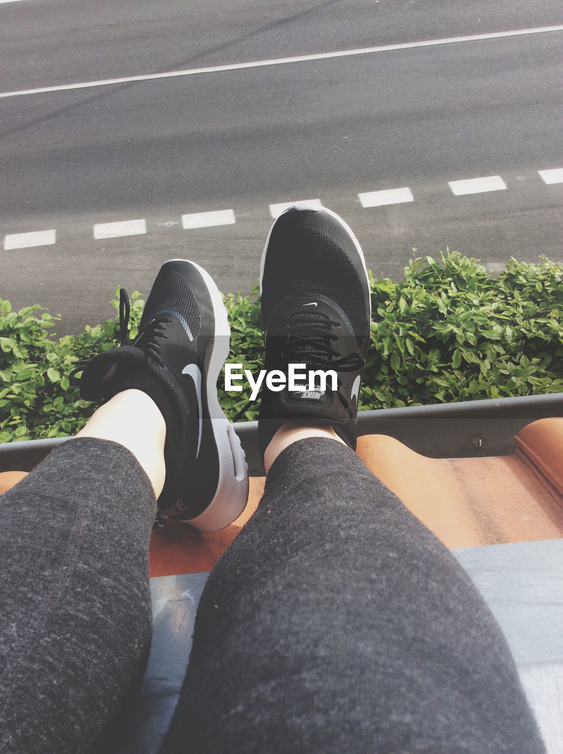 low section, person, shoe, personal perspective, jeans, footwear, lifestyles, street, road, human foot, transportation, standing, men, leisure activity, high angle view, day, sitting
