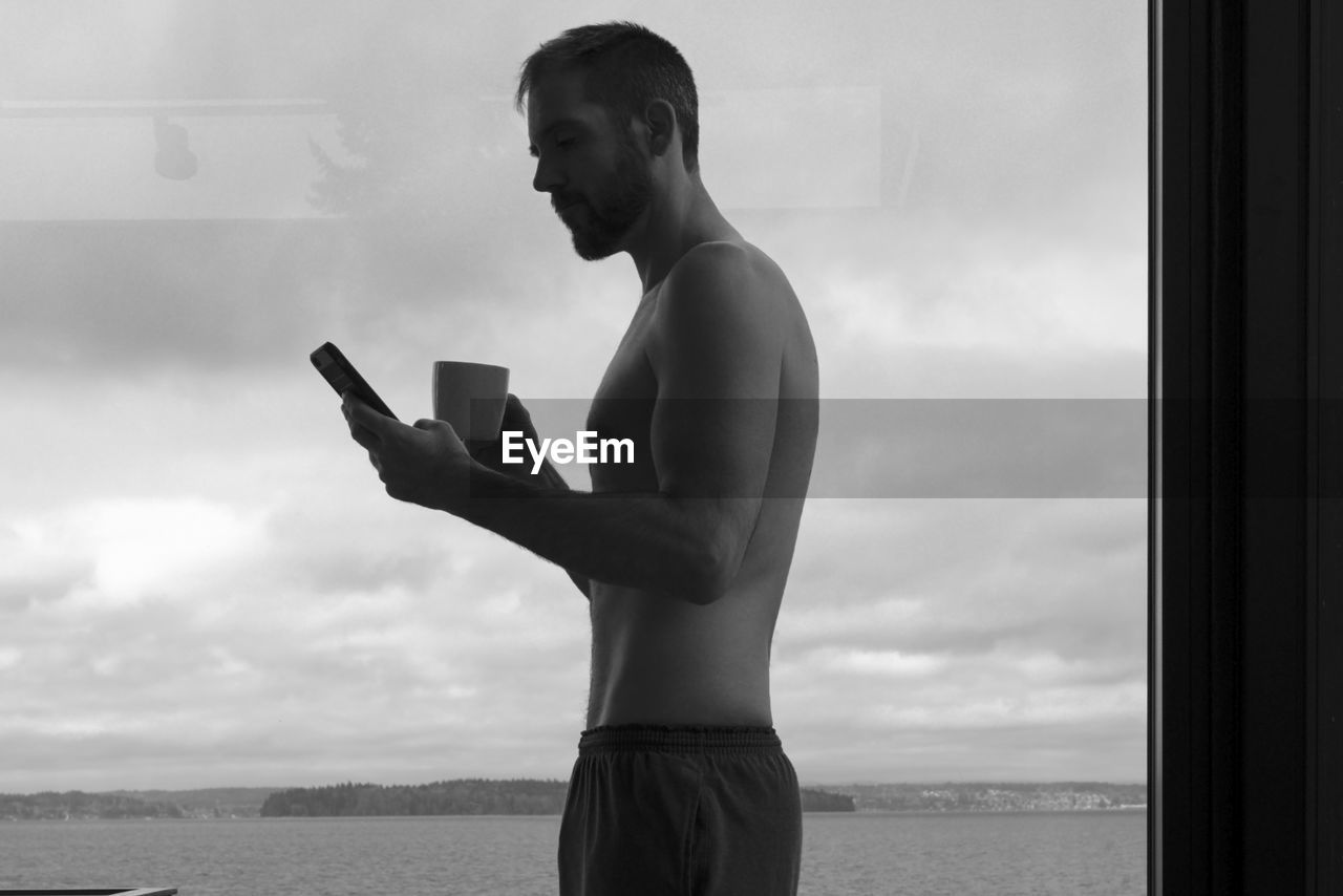 one person, standing, sky, real people, shirtless, cloud - sky, holding, young men, side view, lifestyles, young adult, technology, wireless technology, three quarter length, communication, day, men, water, leisure activity, outdoors