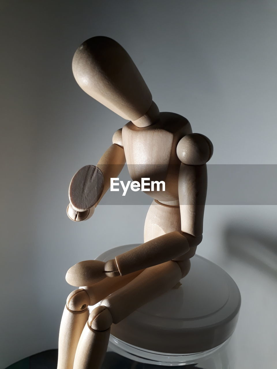 figurine, indoors, human representation, mannequin, human hand, holding, representation, hand, close-up, human body part, studio shot, focus on foreground, gray, male likeness, one person, art and craft, still life, wood - material