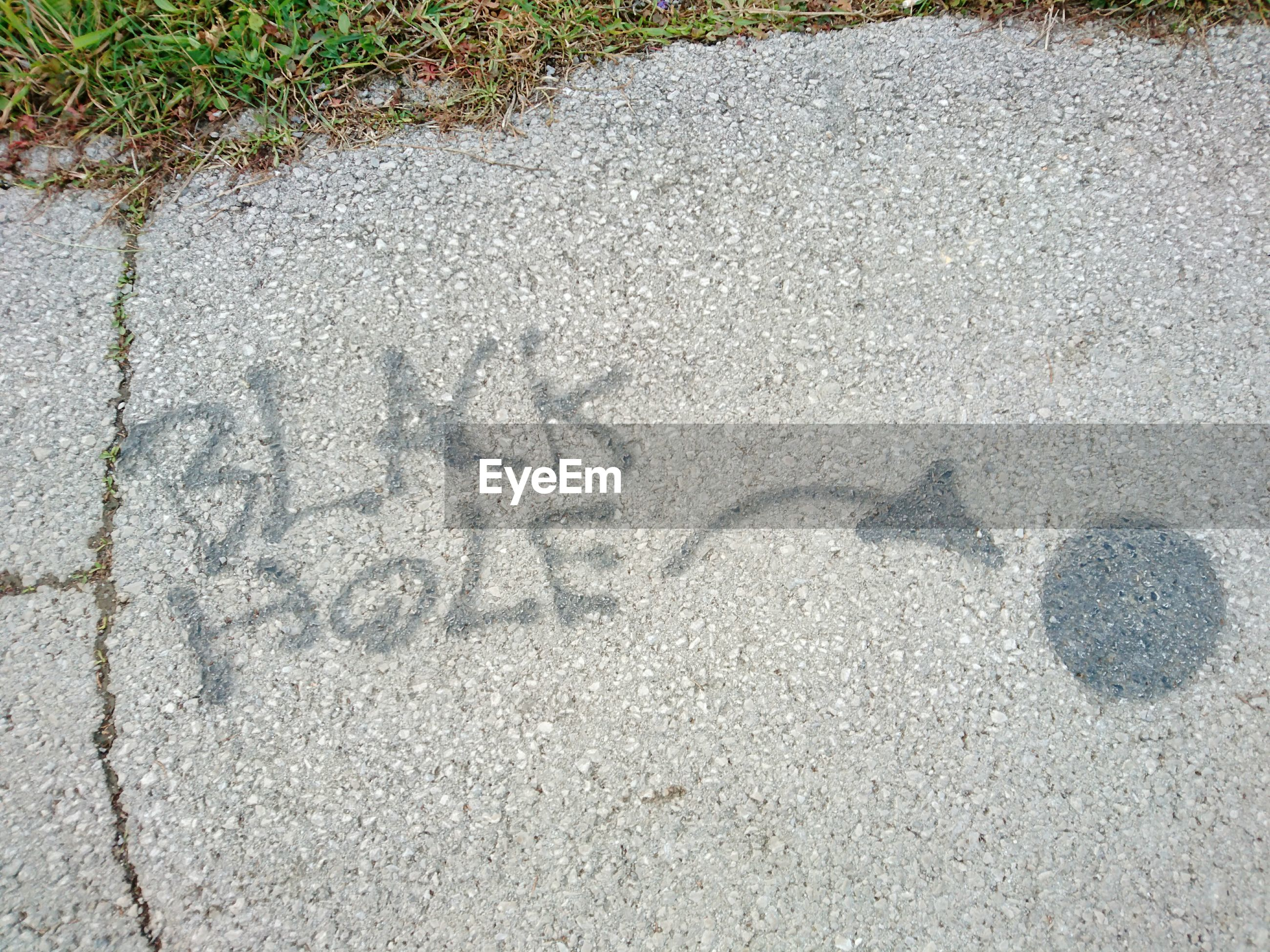 High angle view of text with arrow symbol on road
